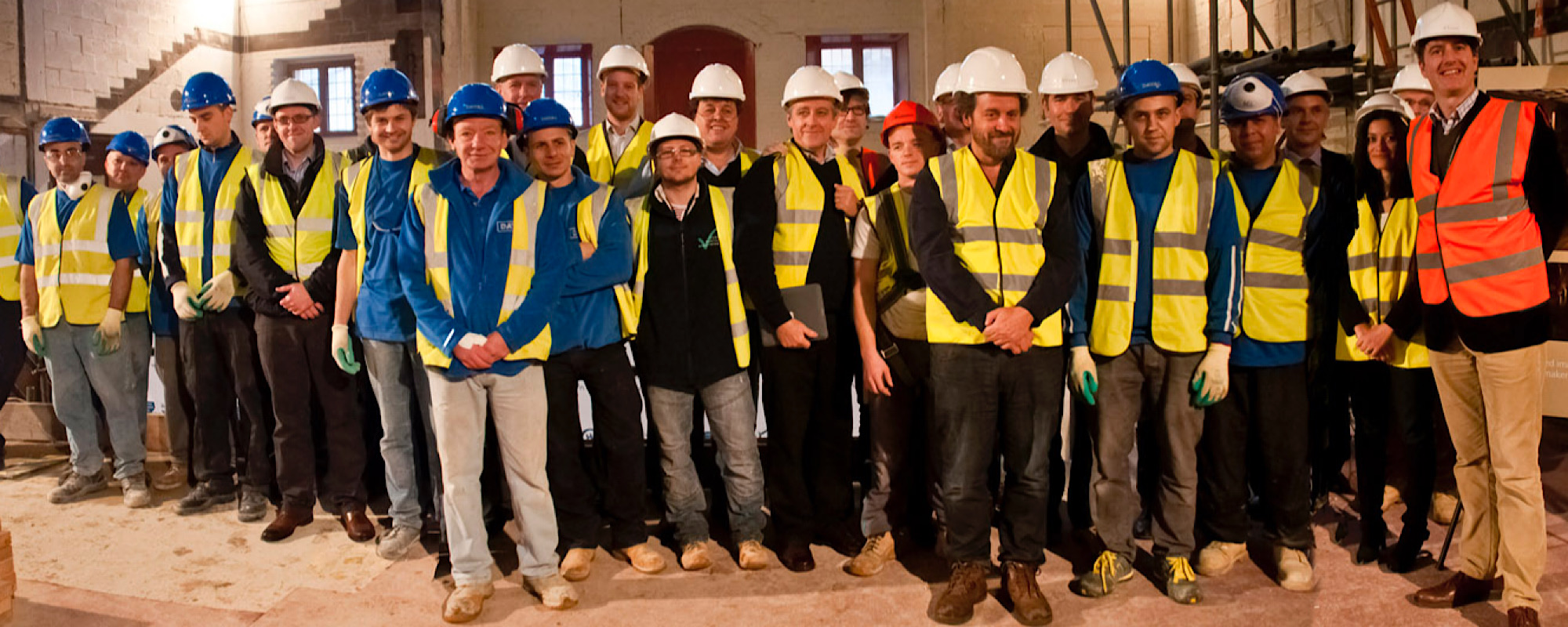 A large group of people in high visibility jackets and hard hats stand on an indoor construction site