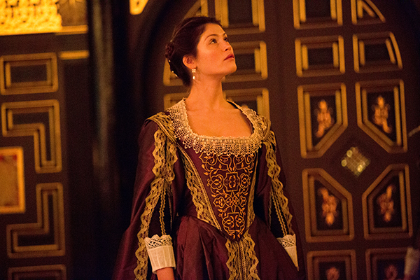 A woman standing in an old fashioned dress on the Sam Wanamaker Playhouse stage