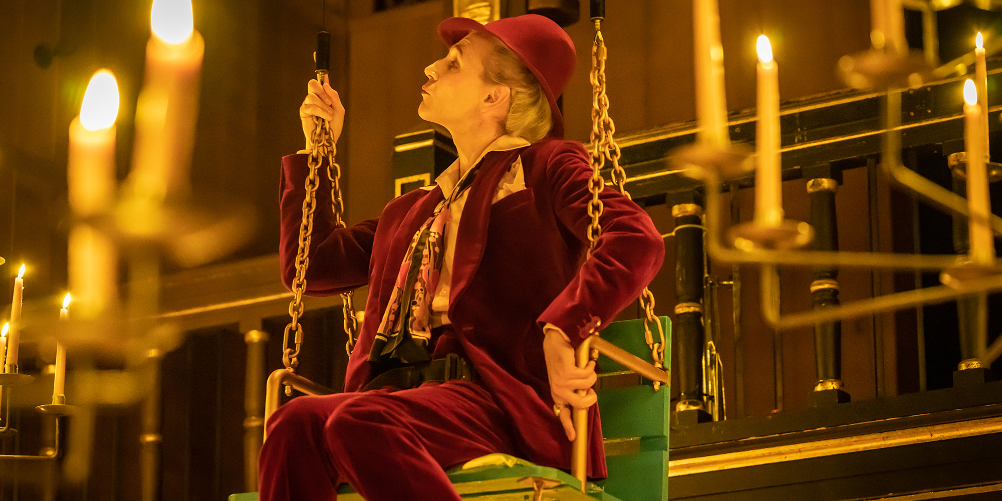 An actor wearing a deep red velvet suit sits on a green swing surrounded by lit candles.