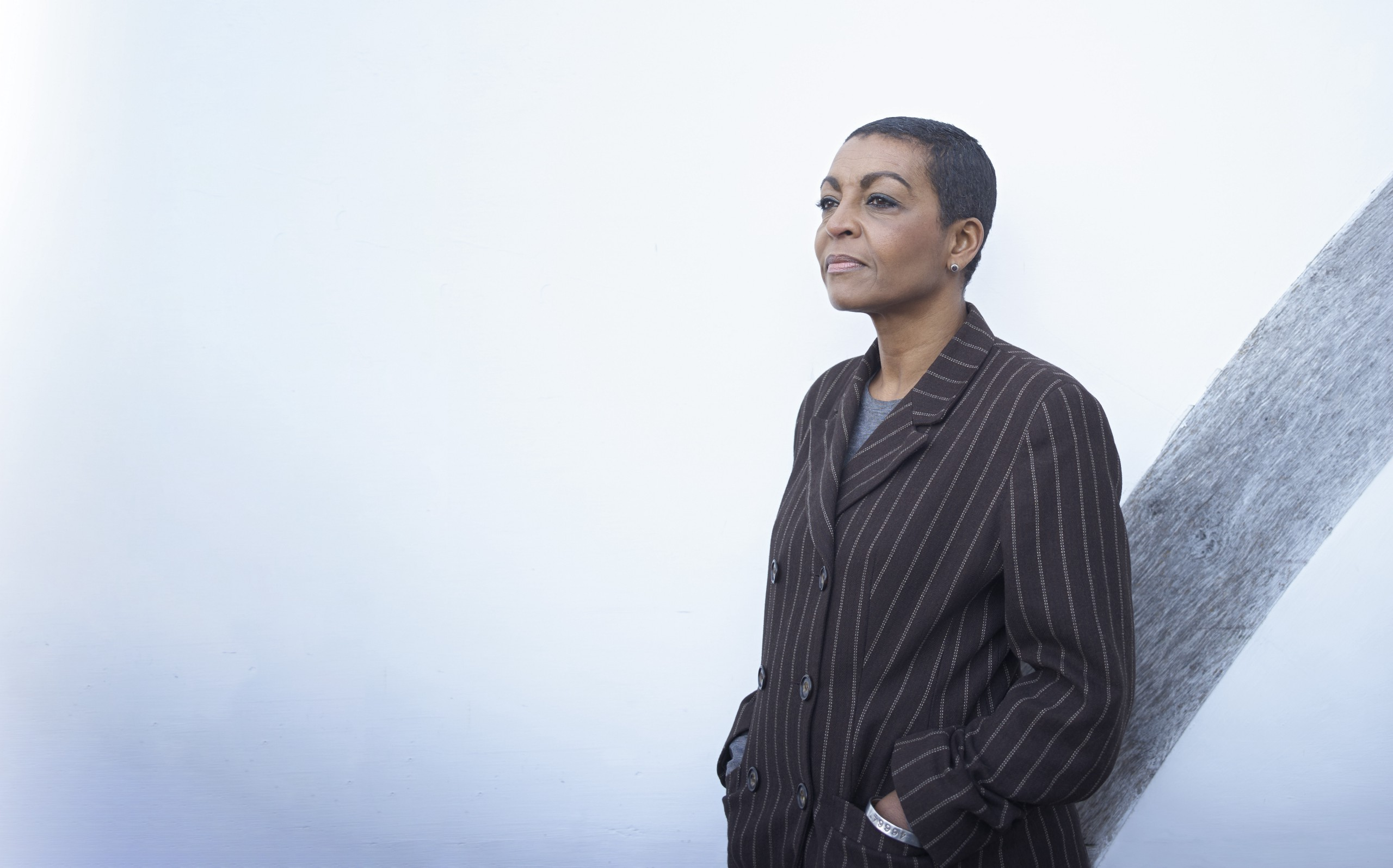 A black woman with short cropped hair stands against a white wall wearing a dark pinstripe suite.