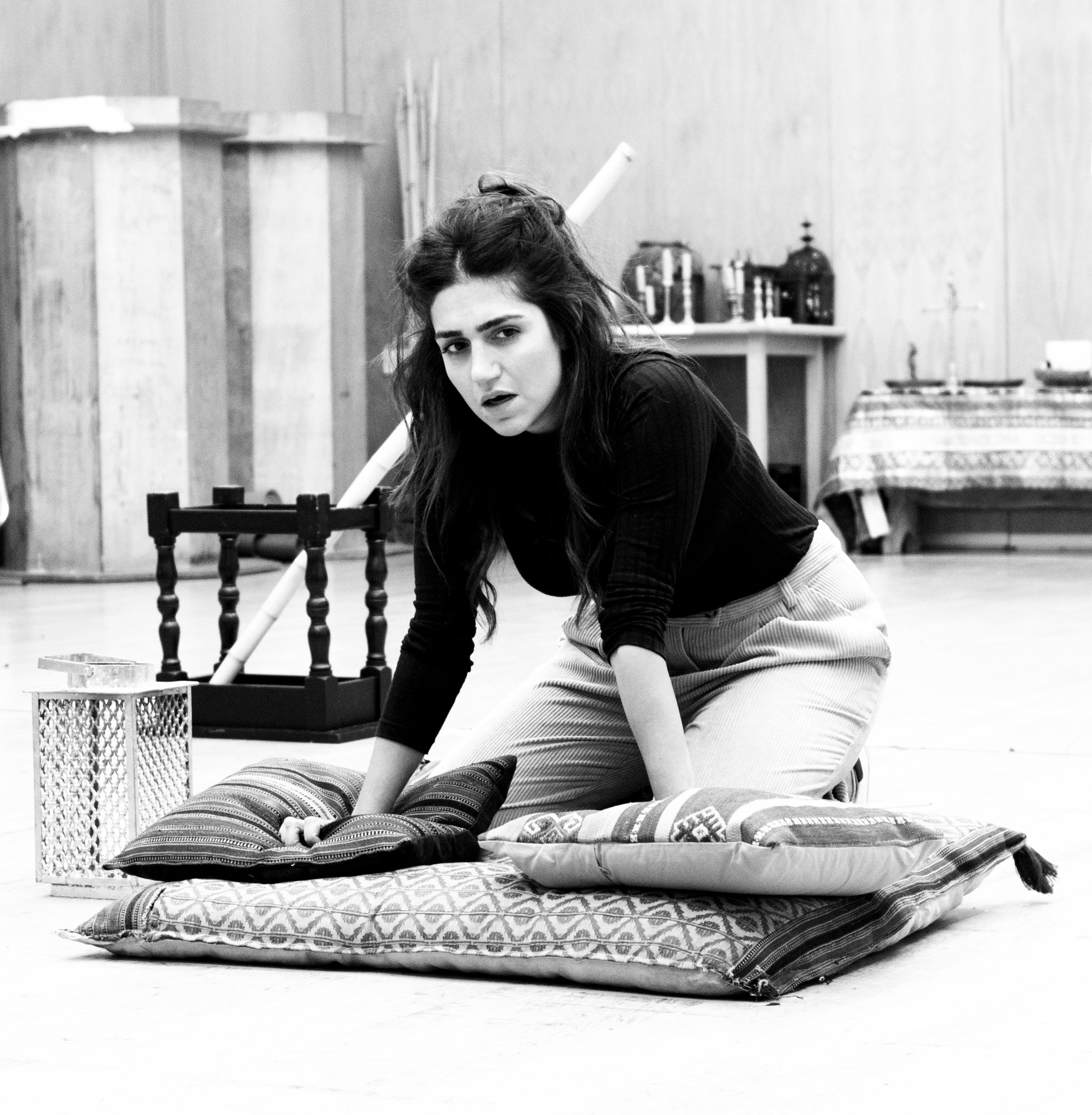 A woman kneeling on a pile of cushions