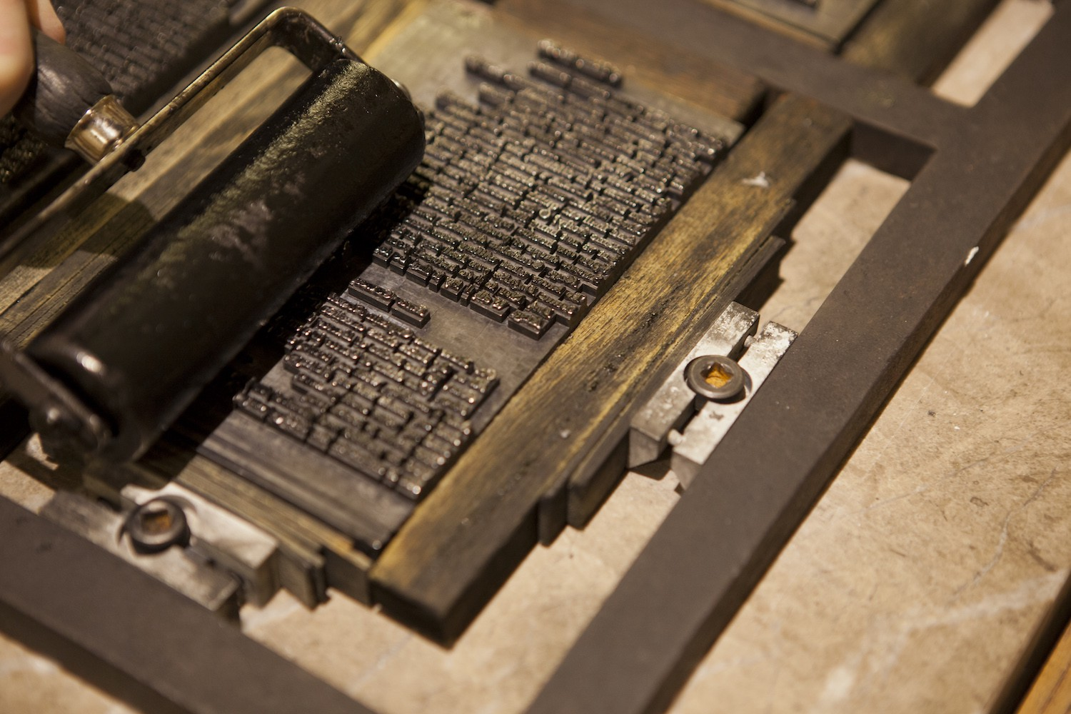 An ink roller running across a template of letters