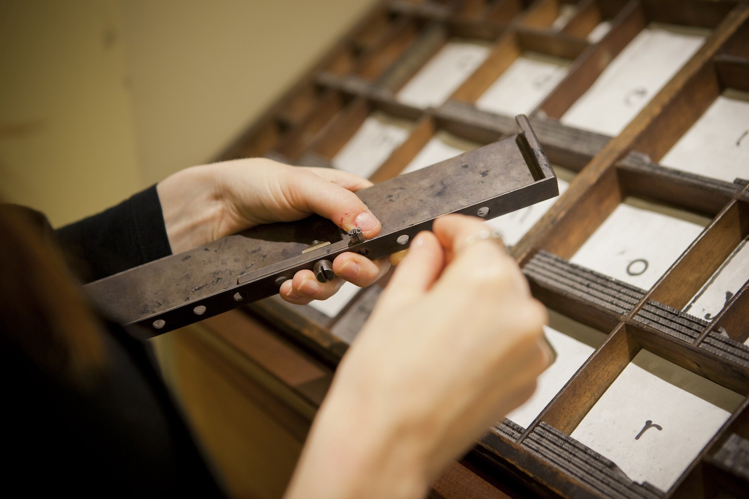 A woman putting letter pieces into a thin metal tray