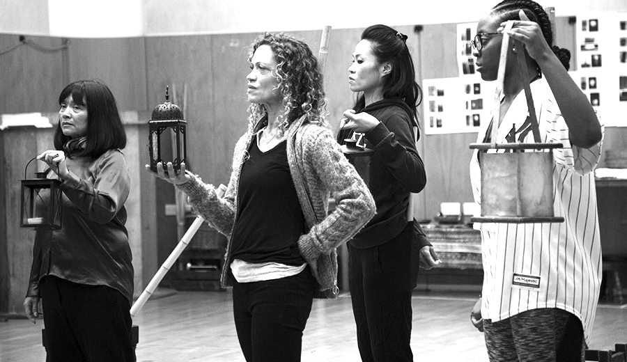 Four women standing holding lanterns in a rehearsal space