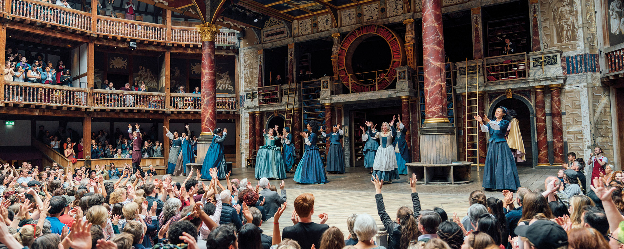 The cast of 'Emilia' gather on stage with their arms in the air, the yard audience also have their arms in the air