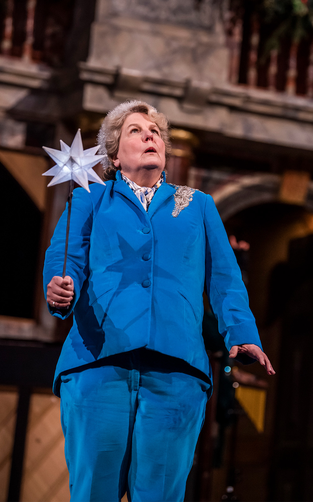 A woman in a blue suit on a stage