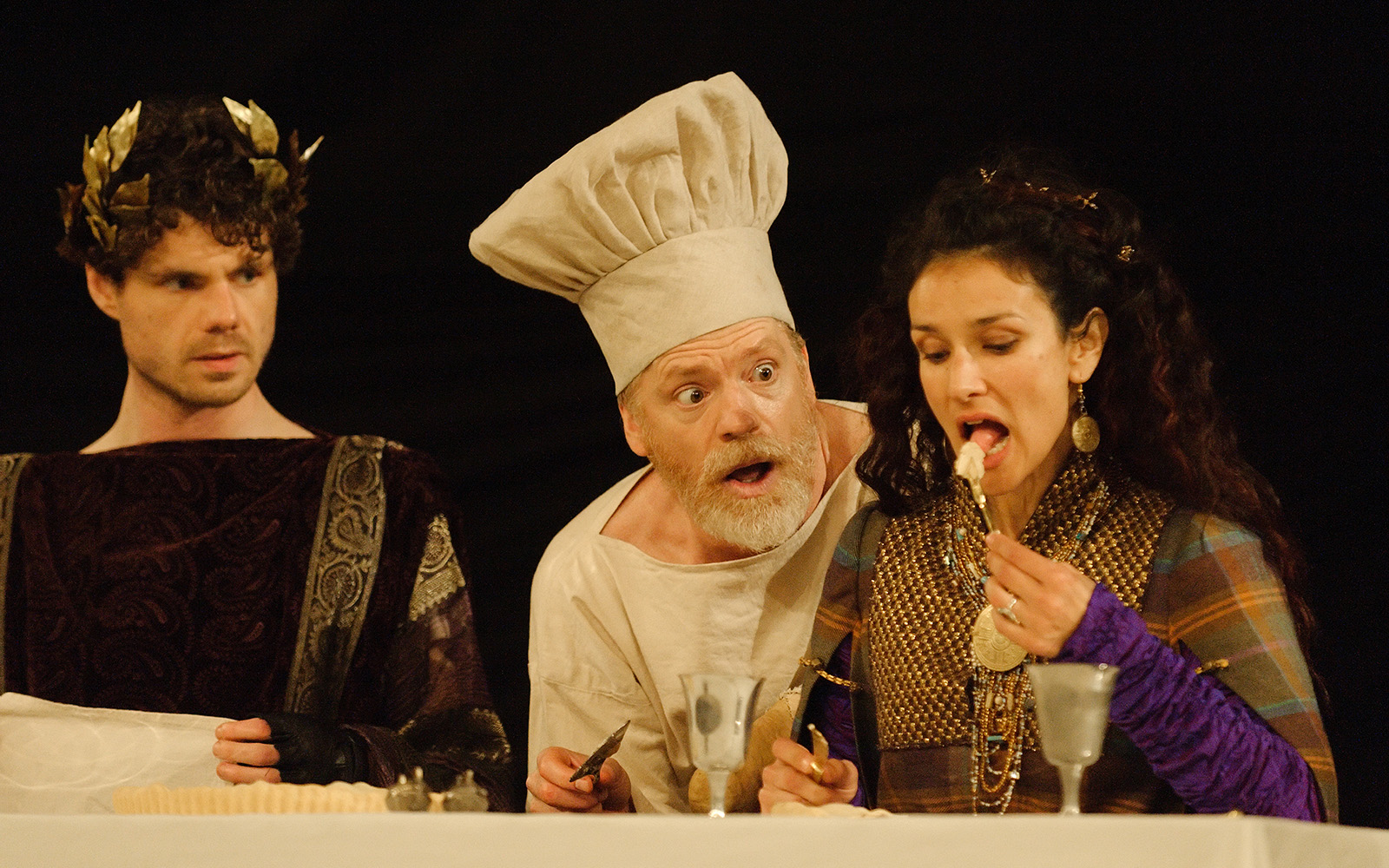 A man wearing a chef's hat watches as a woman raises a forkful of food to her mouth.