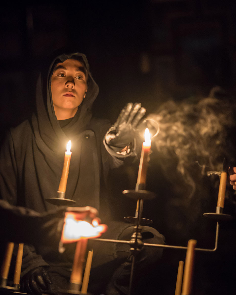 A cloaked man raises his hand to a lit candle.
