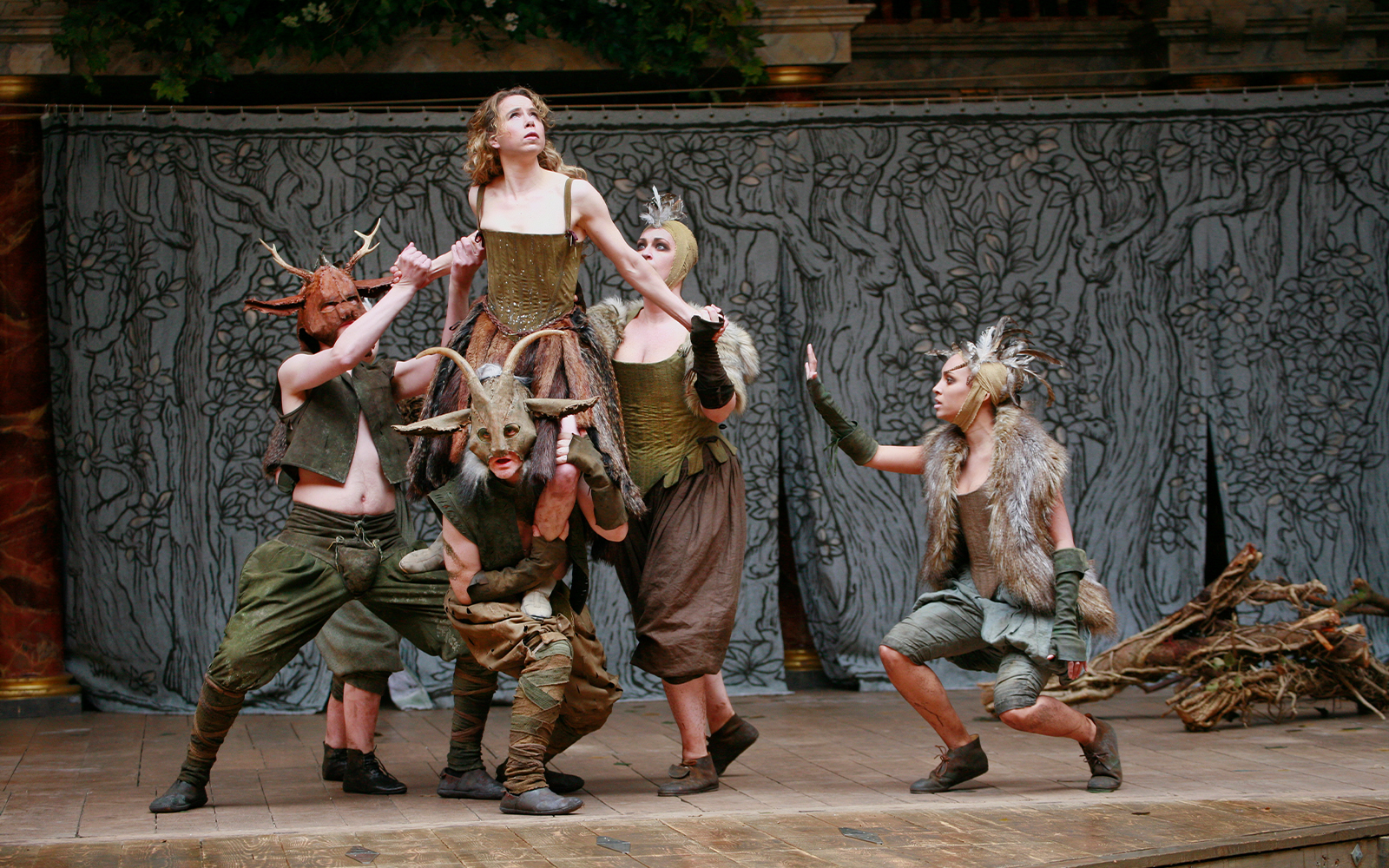 An actress is lifted by a number of other actors as she looks to the sky.