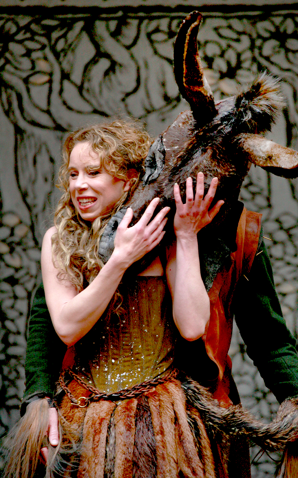 An actress caresses the face of man who has a donkey's head.