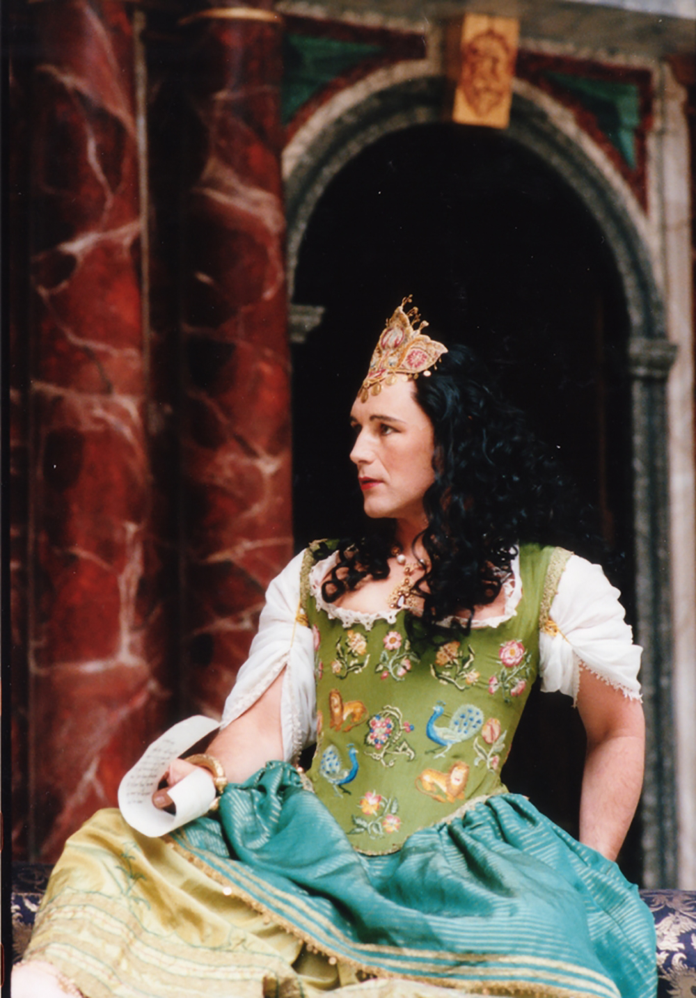 A man wearing a green corset dress sits on the Globe Theatre stage.