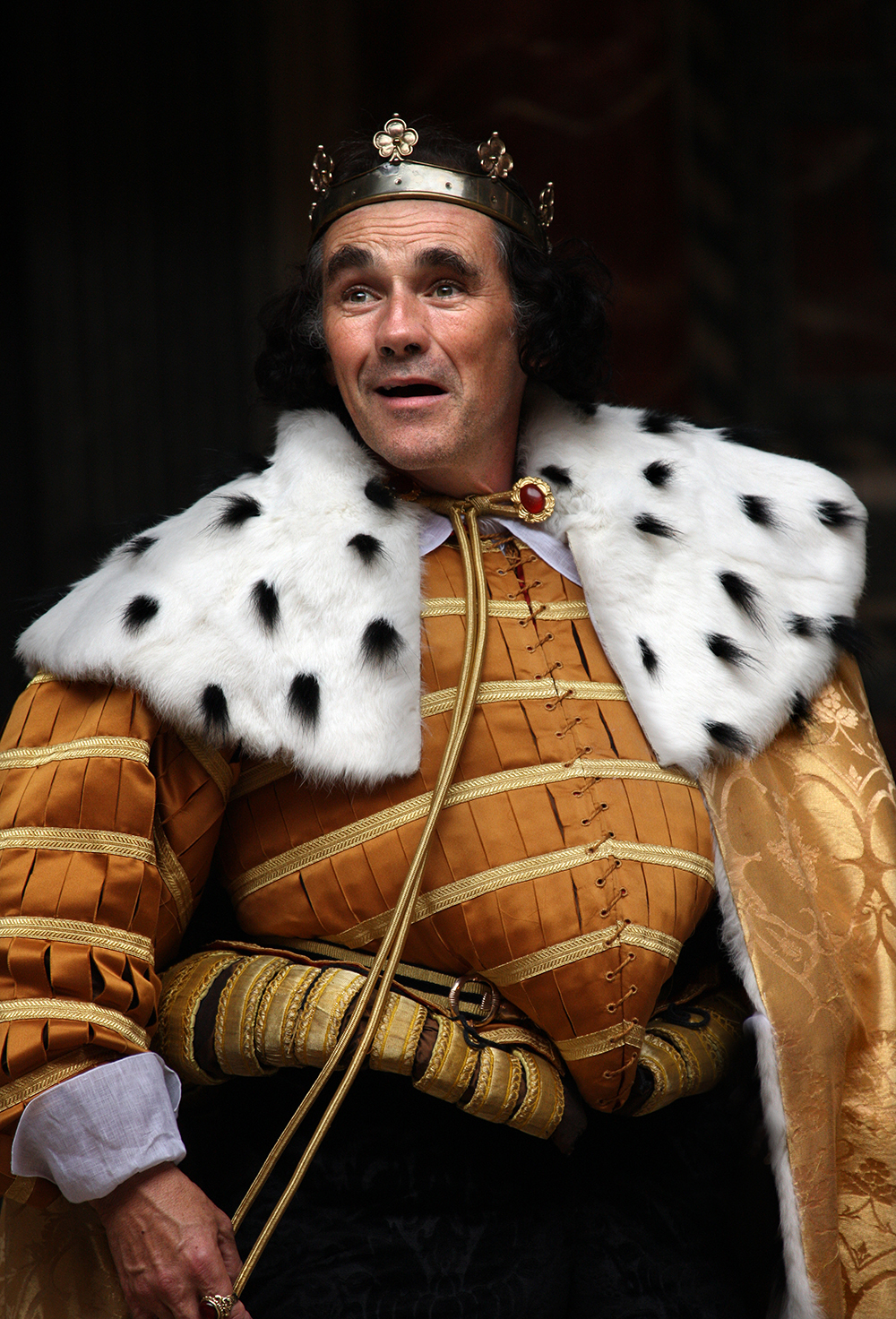 A man wearing an ermine royal cloak and golden doublet smiles.