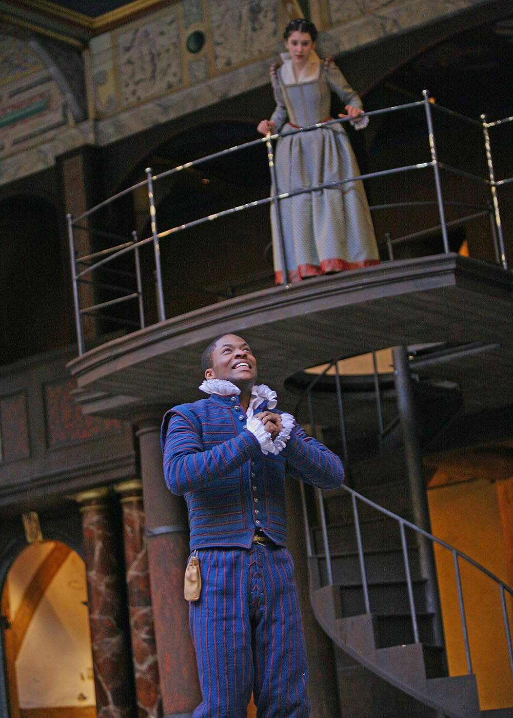 A young woman watches from a balcony as a young man clutches his hands to his chest, besotted.