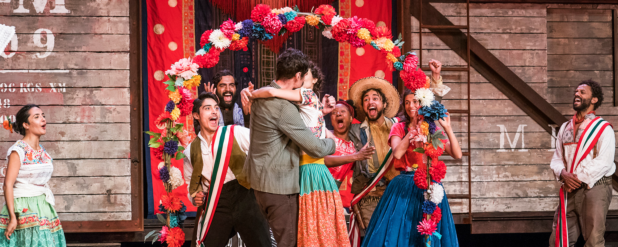 Beatrice and Benedick embrace and kiss surrounded by onlookers. The stage is full of brightly coloured decorations and costumes.