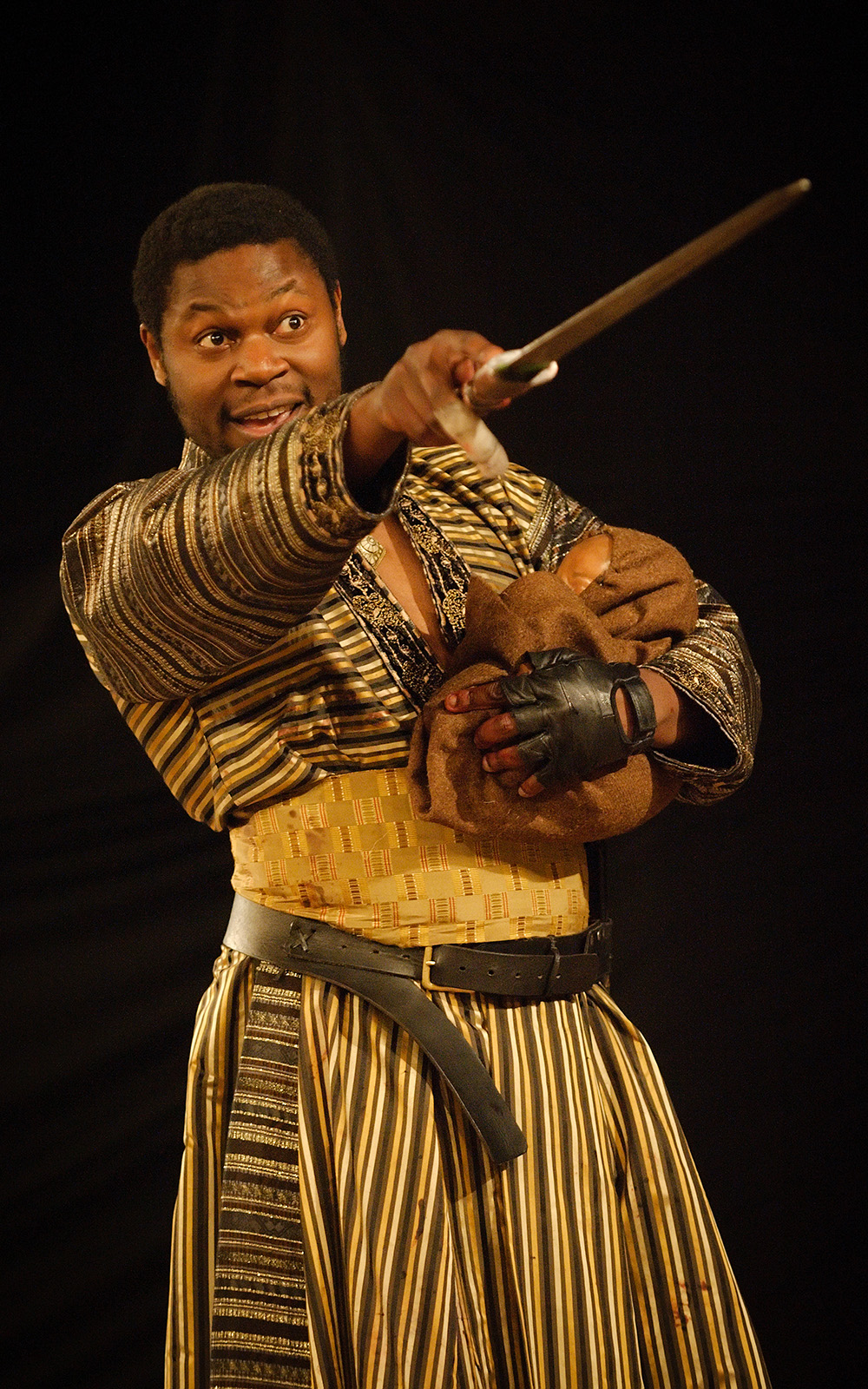 A man holds a bundle in his left arm, whilst pointing his sword at another.