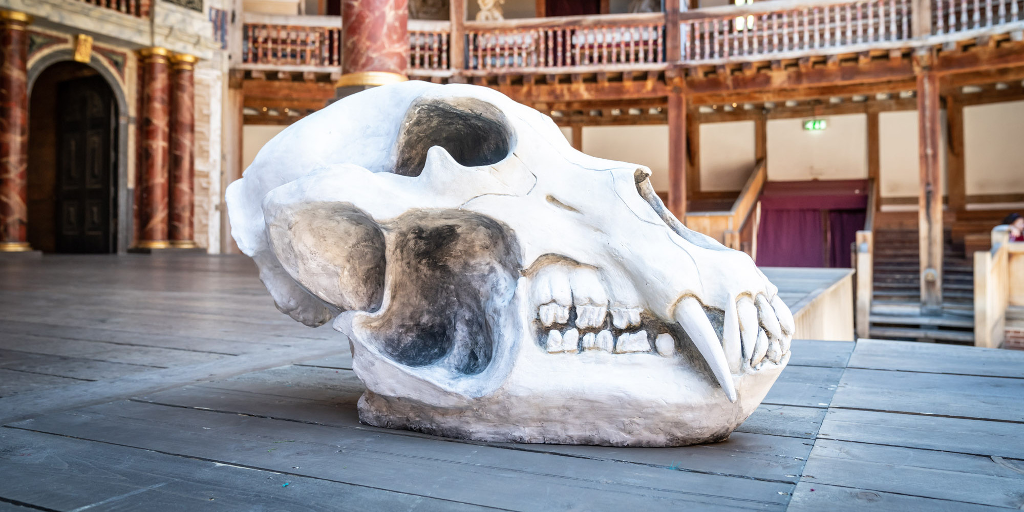 An immense bear skull prop sits on the Globe Theatre stage.