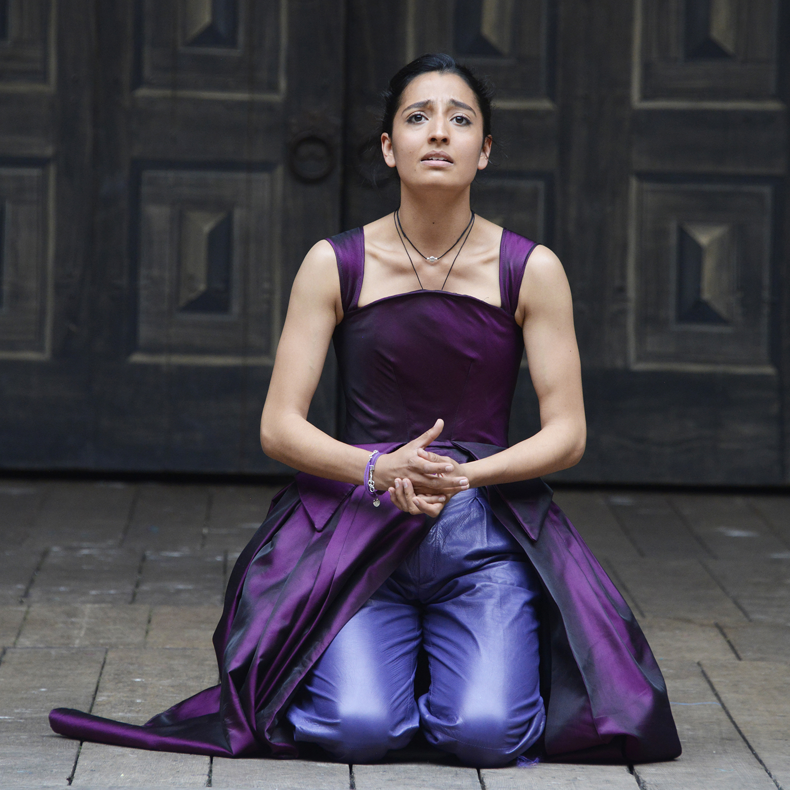 A woman wearing a bright purple gown kneels on the Globe stage, her hands clasped.