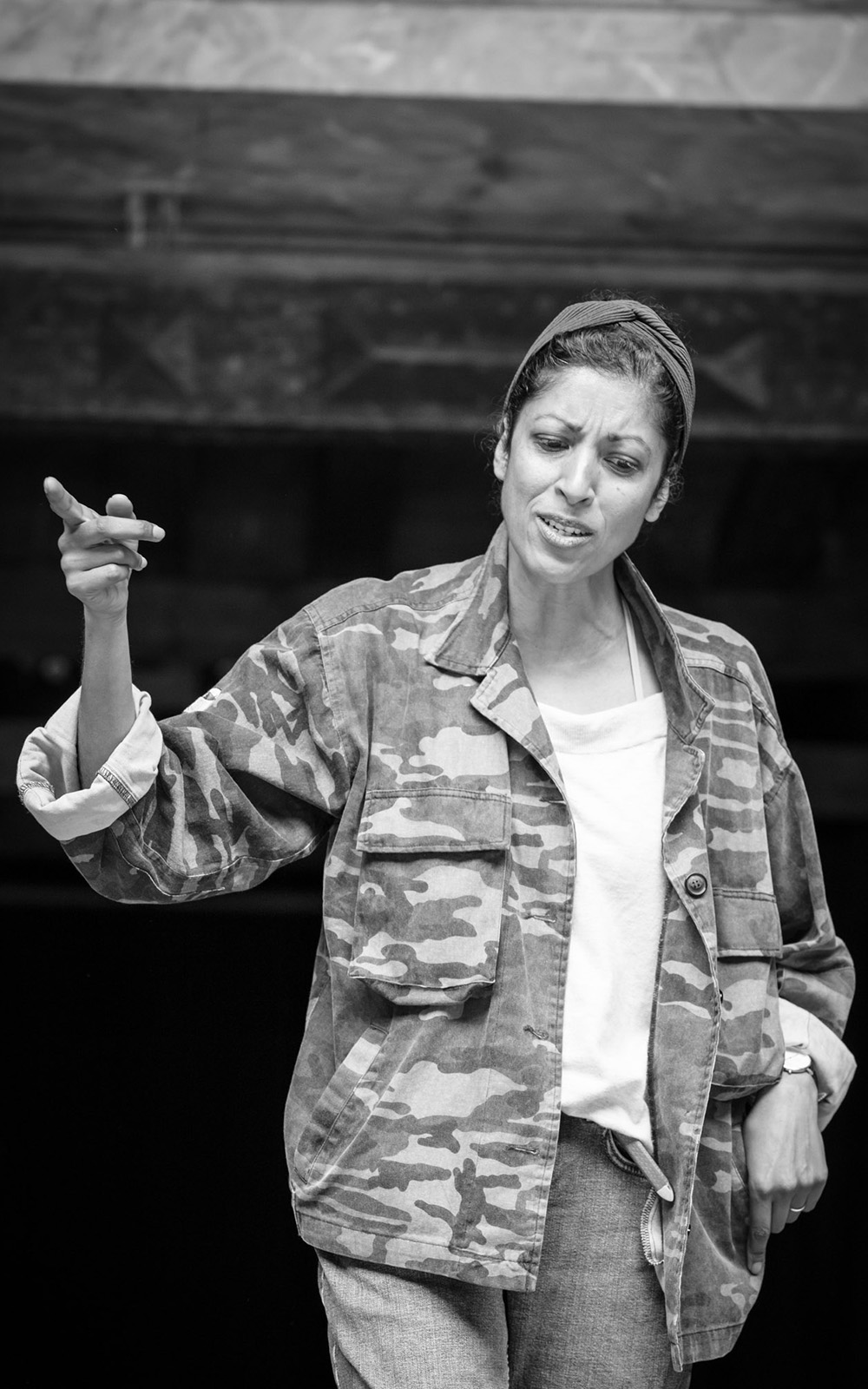 A woman wearing a green cargo jacket looks down disgruntled whilst pointing her finger out.