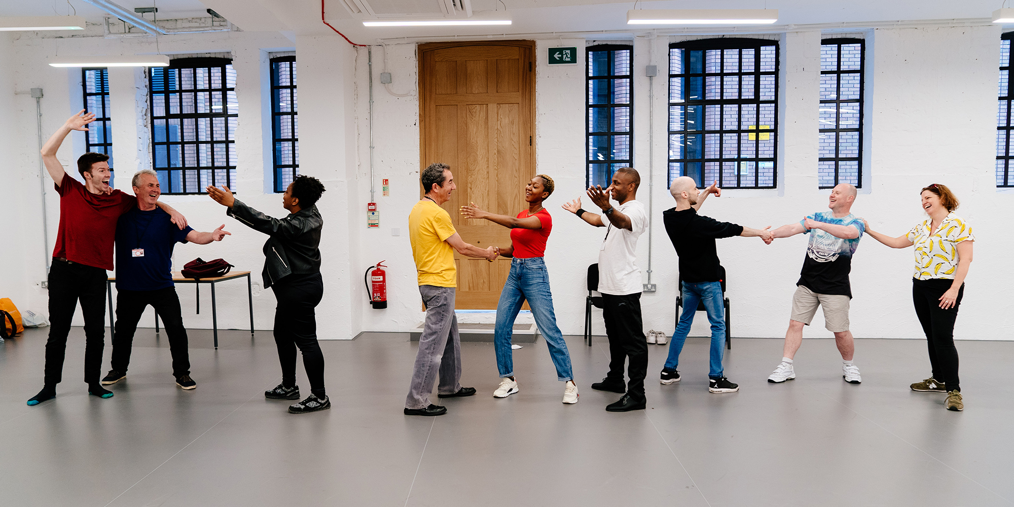 A chain of people stand in a row in a rehearsal room, arms outstretched and smiling at each other.