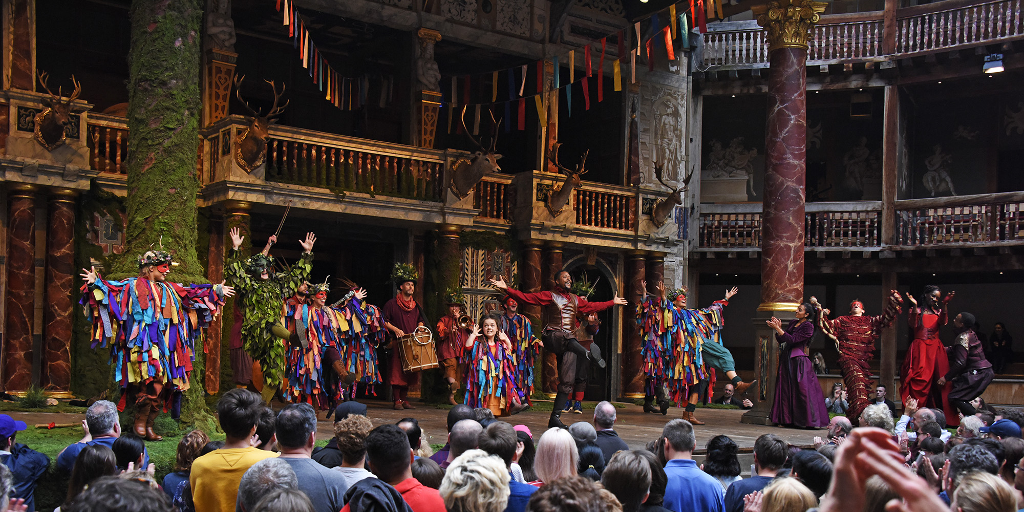 A group of actors wearing brightly coloured costumes dance on the Globe Theatre stage