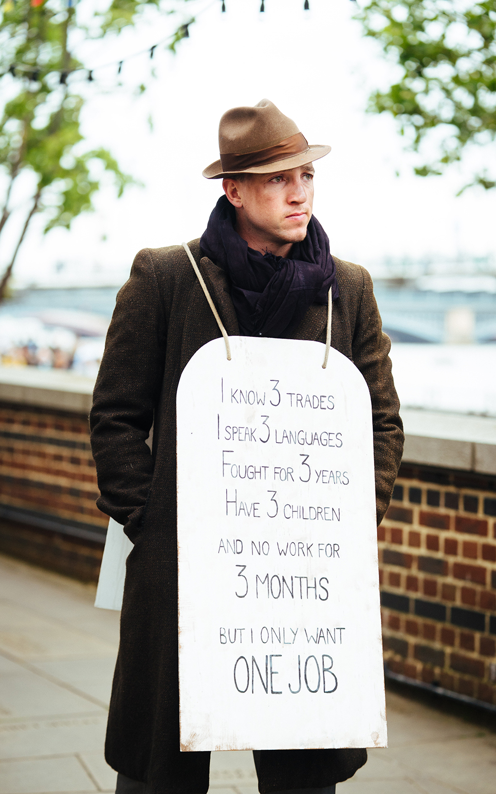 A man wearing a brown overcoat and hat stands glum with a billboard, outside.