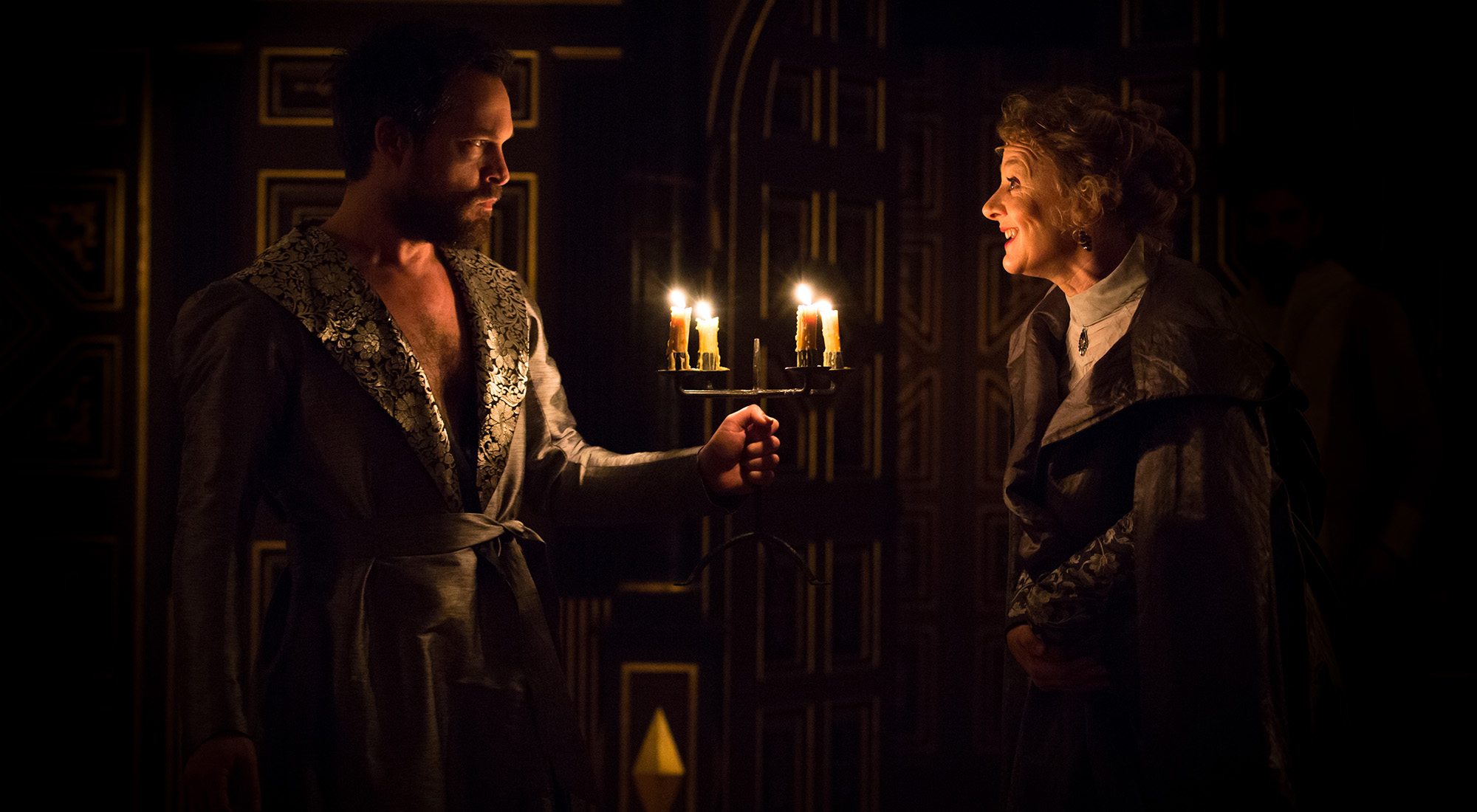Two actors stand opposite each other with candles in between them