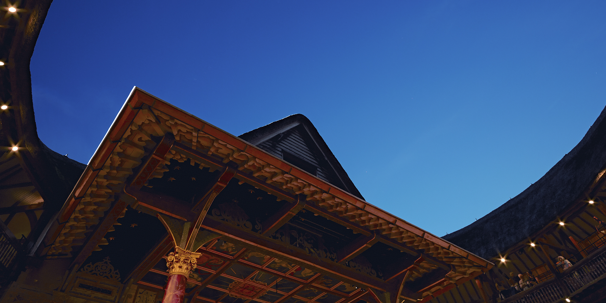 A bright blue evening sky above a circular timber theatre, with pointed thatched roof.
