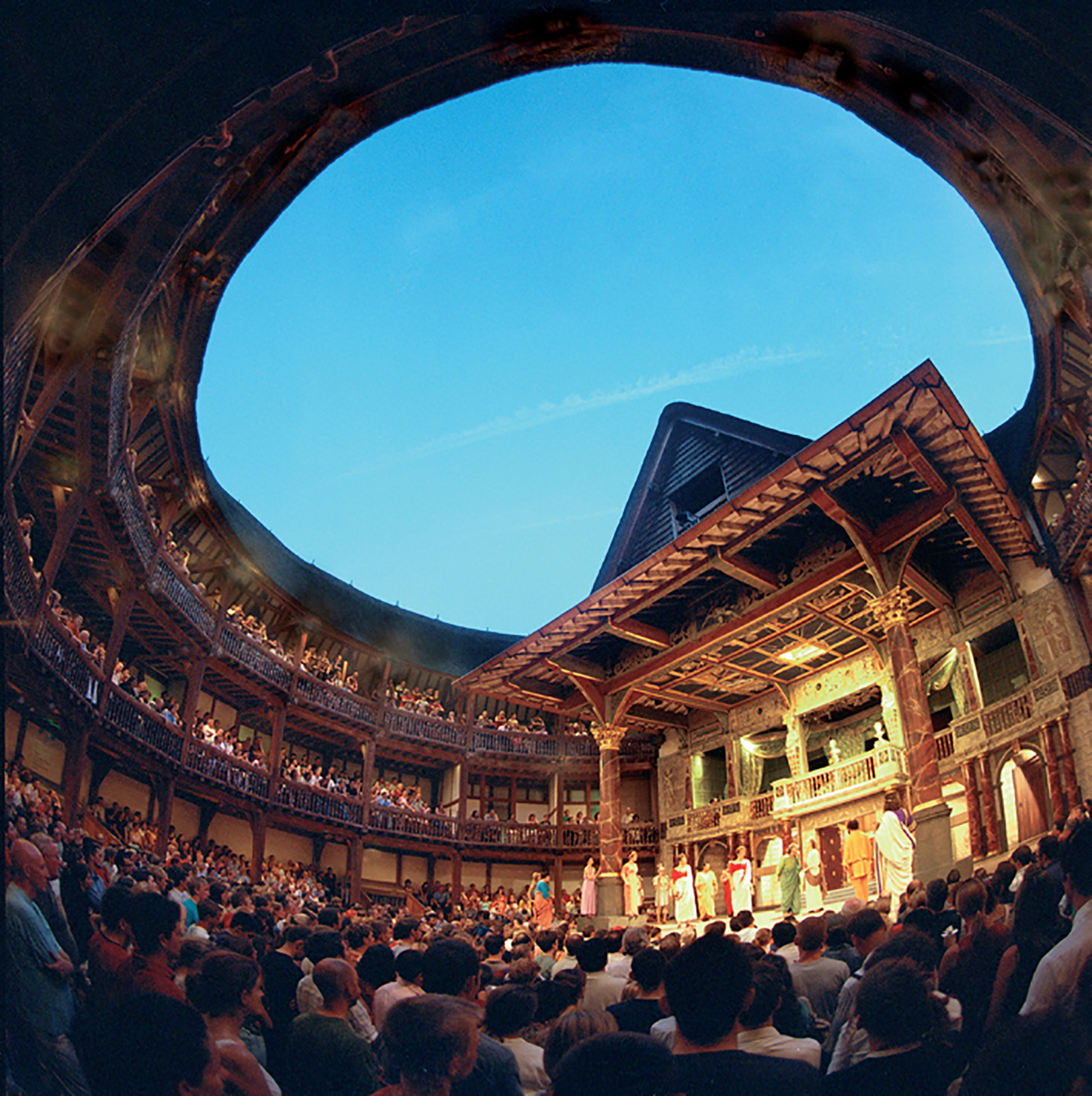A circular inside photograph of a timber structure theatre, filled with audiences.
