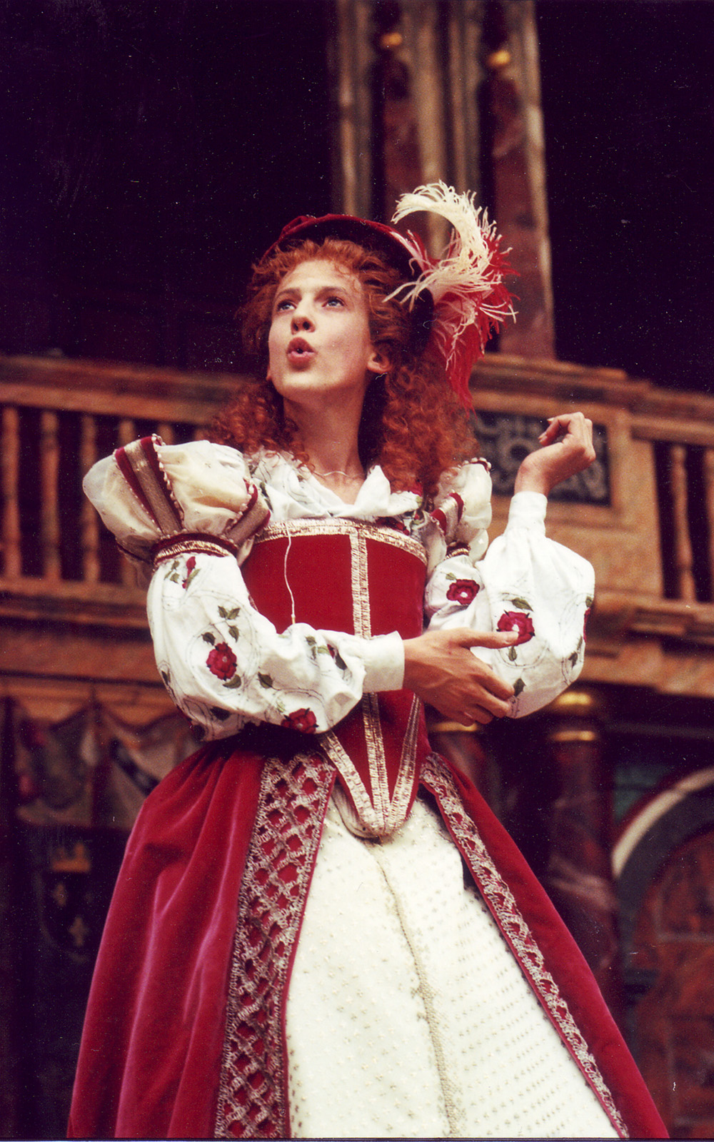 An actor wears a bright red traditional Elizabethan dress, with corset, puffed sleeves, and full skirt.