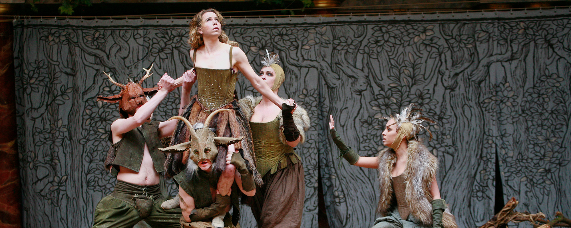 An actress is lifted by four other actors in woodland fairy costumes