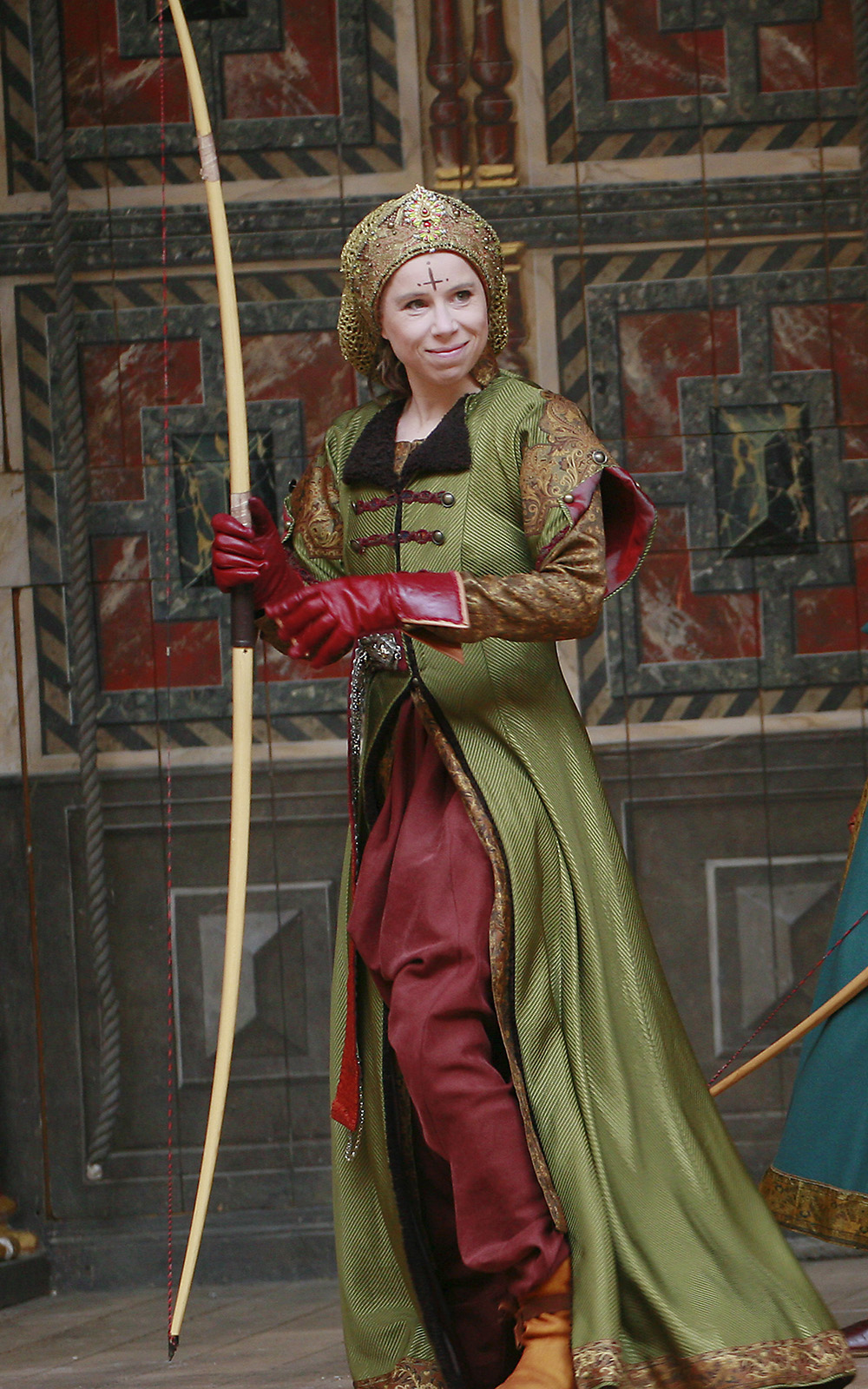 An actor wearing a green hunting coat holds a long bow.