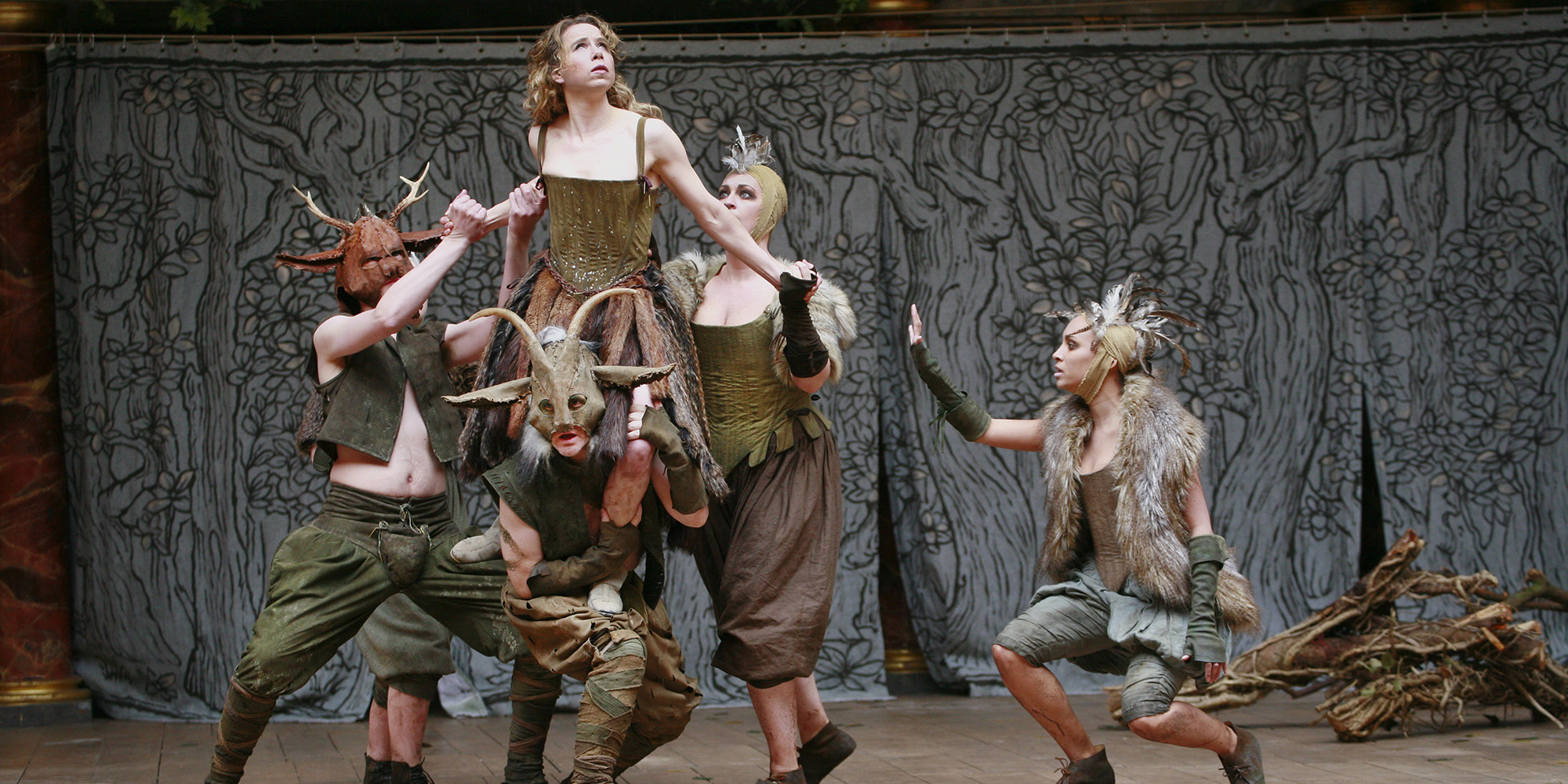 A woman wearing a green corset dress is lifted into the air by a group of people wearing fur and antlers.