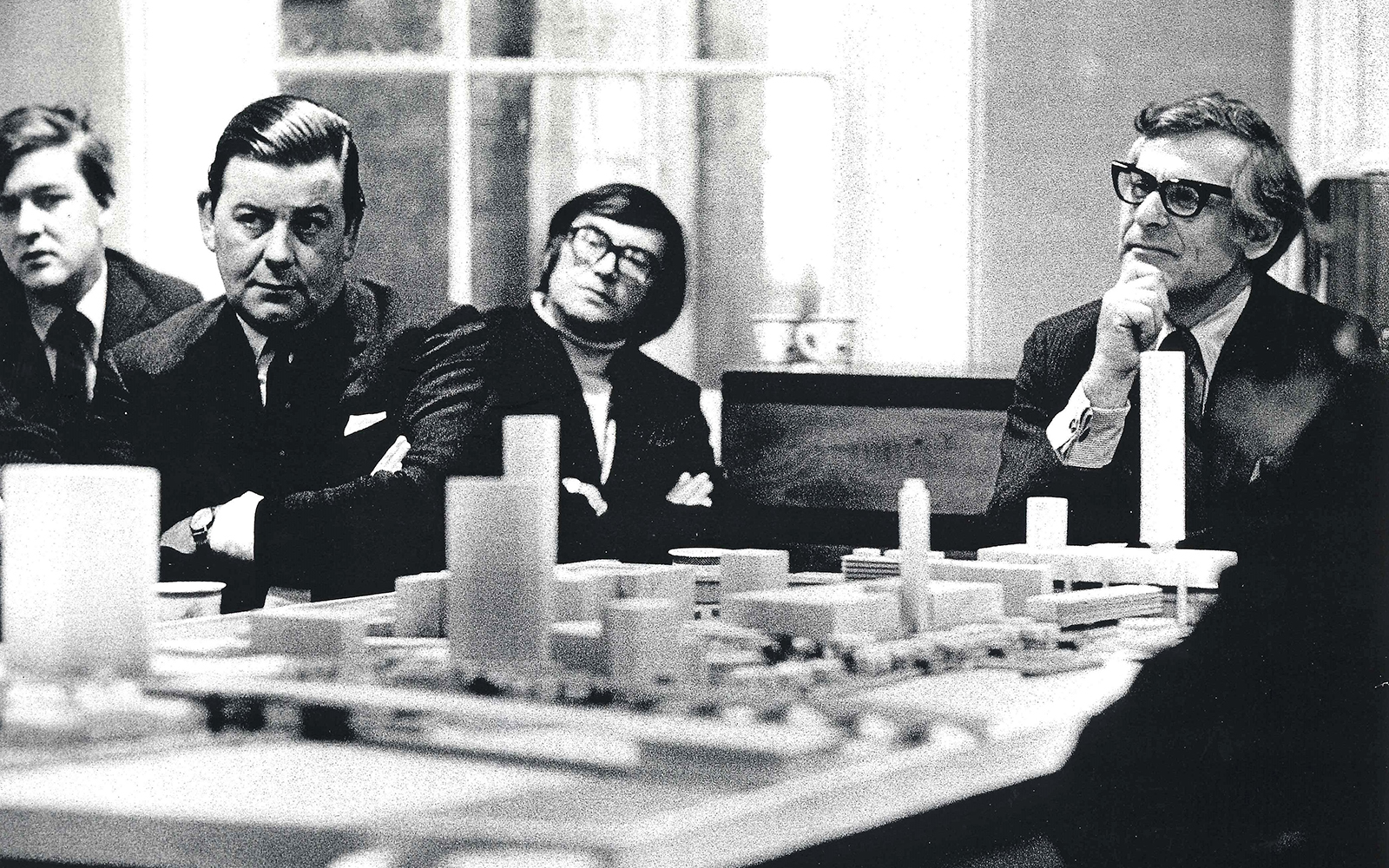 A group of men sit around a table, with a model plan of buildings.