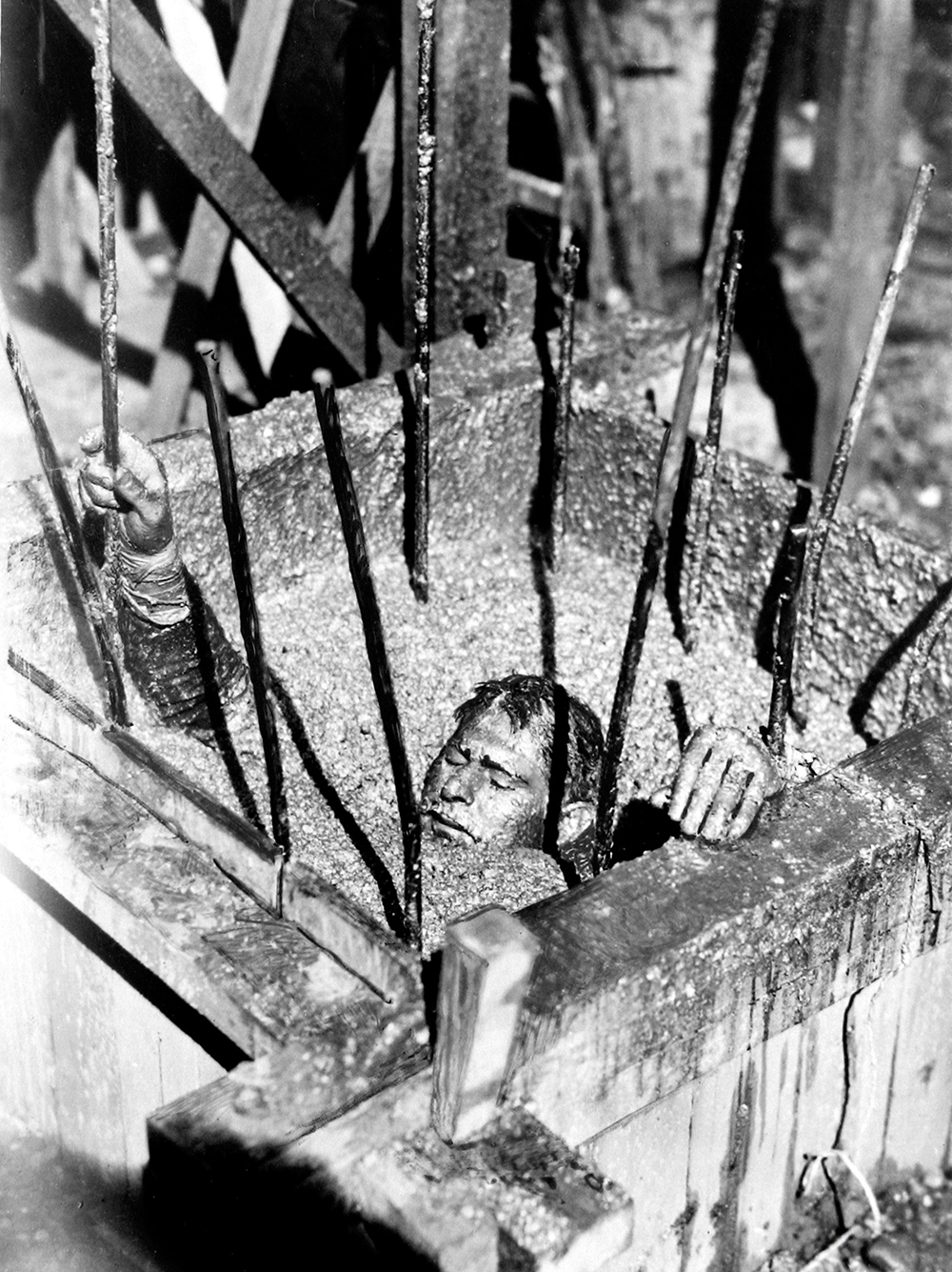 A man is buried to his neck in gravel, behind bars.
