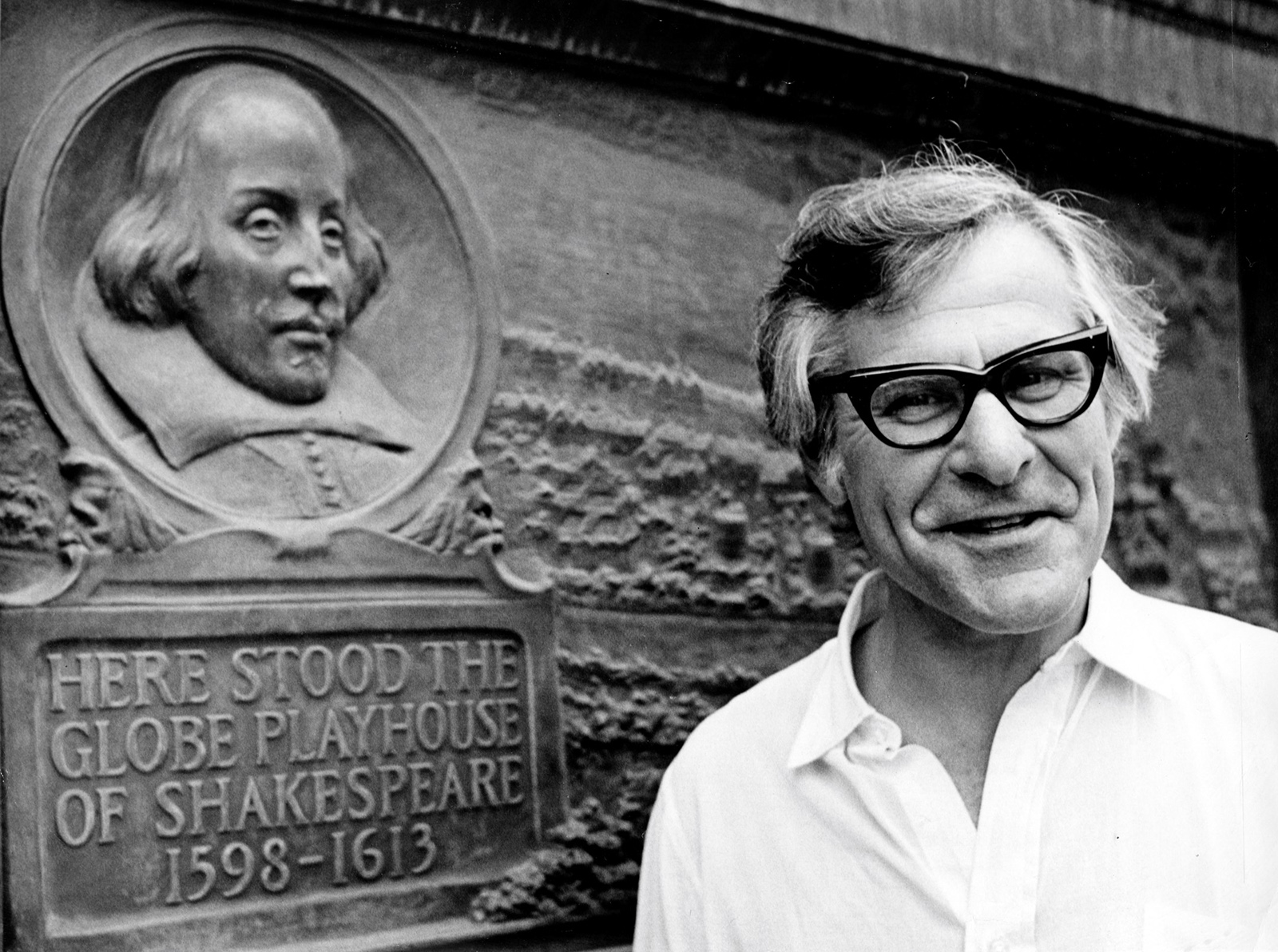 A man wearing thick-framed glasses stands by a plaque marking the location of the original Globe Theatre.