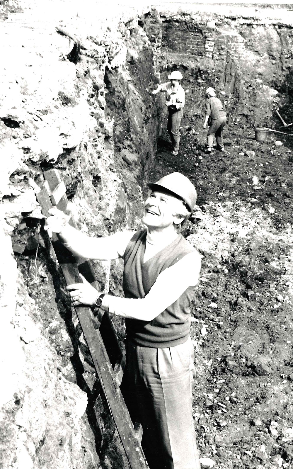 A man stands on a ladder in a ditch of mud and dirt, wearing a hard hat.