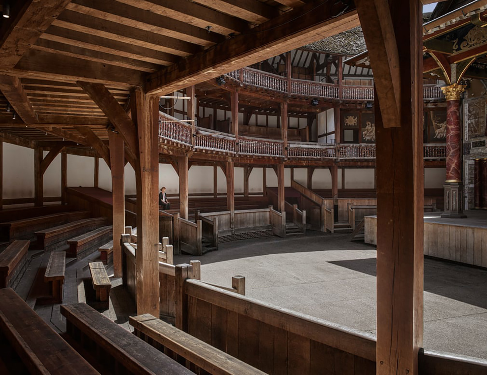 A woman sits in the lower gallery of a circular timber theatre, which lays empty.