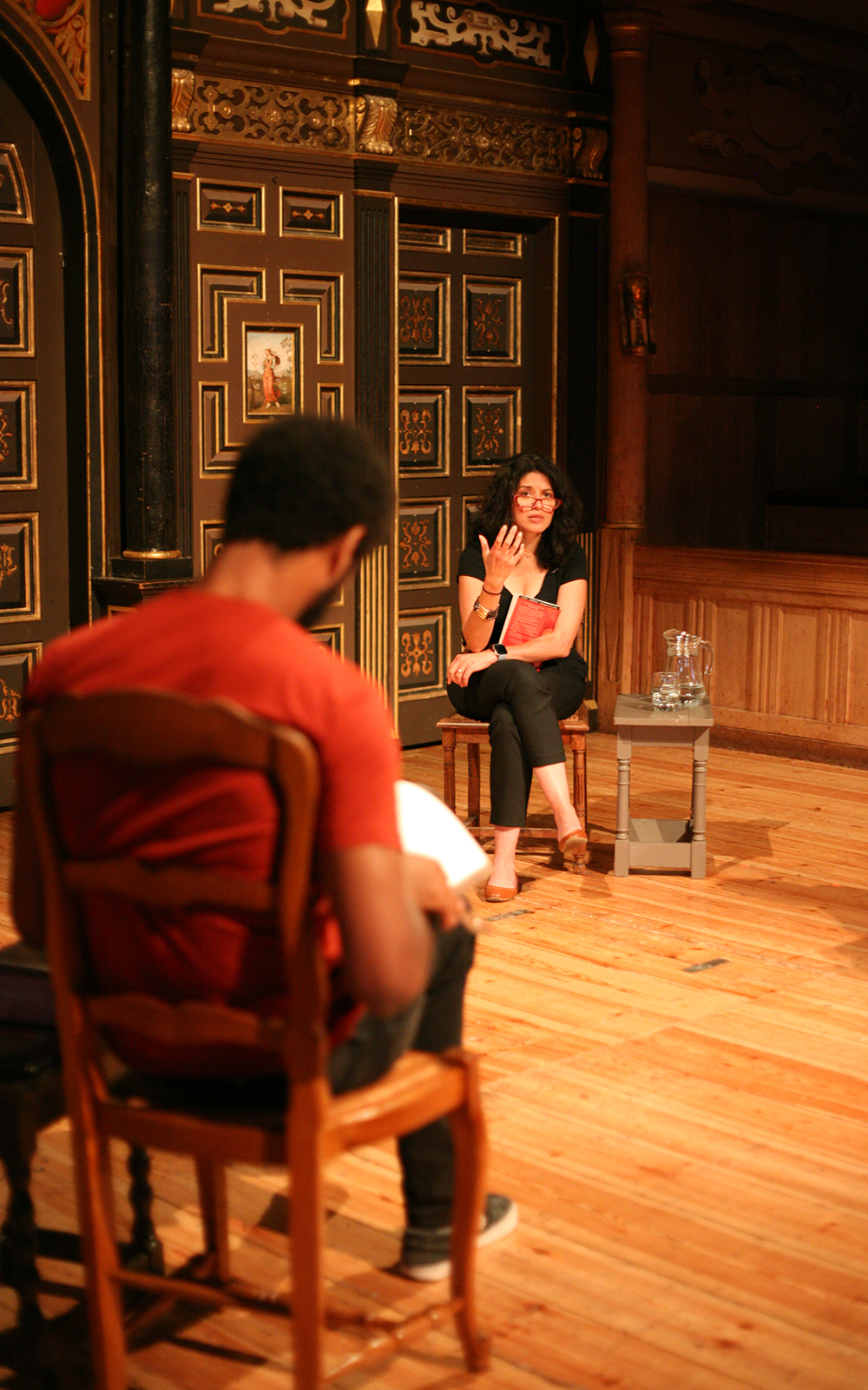 A woman talks to a group onstage as they sit on chairs