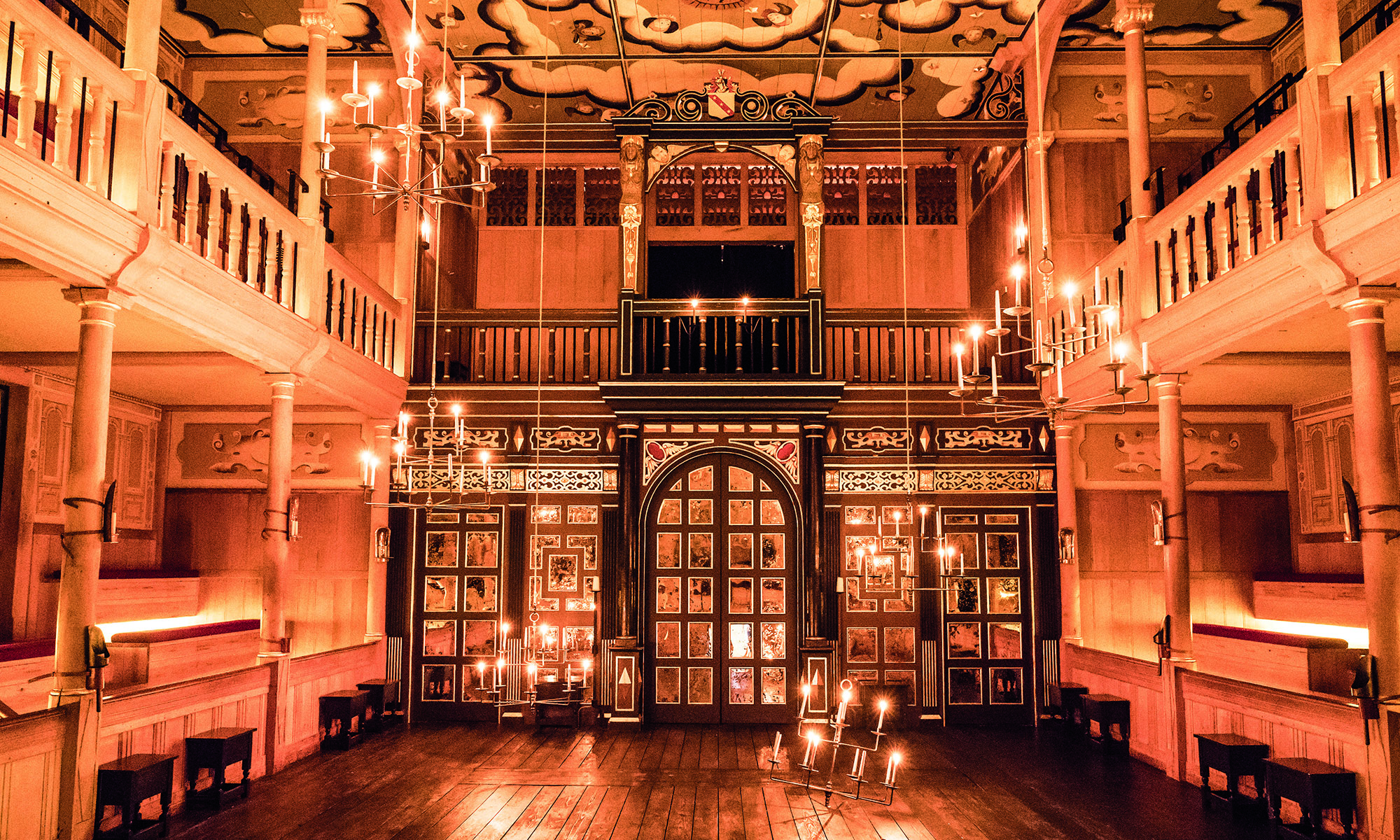 The candlelit interior of an indoor playhouse, with dark wooden panelling and a golden glow.