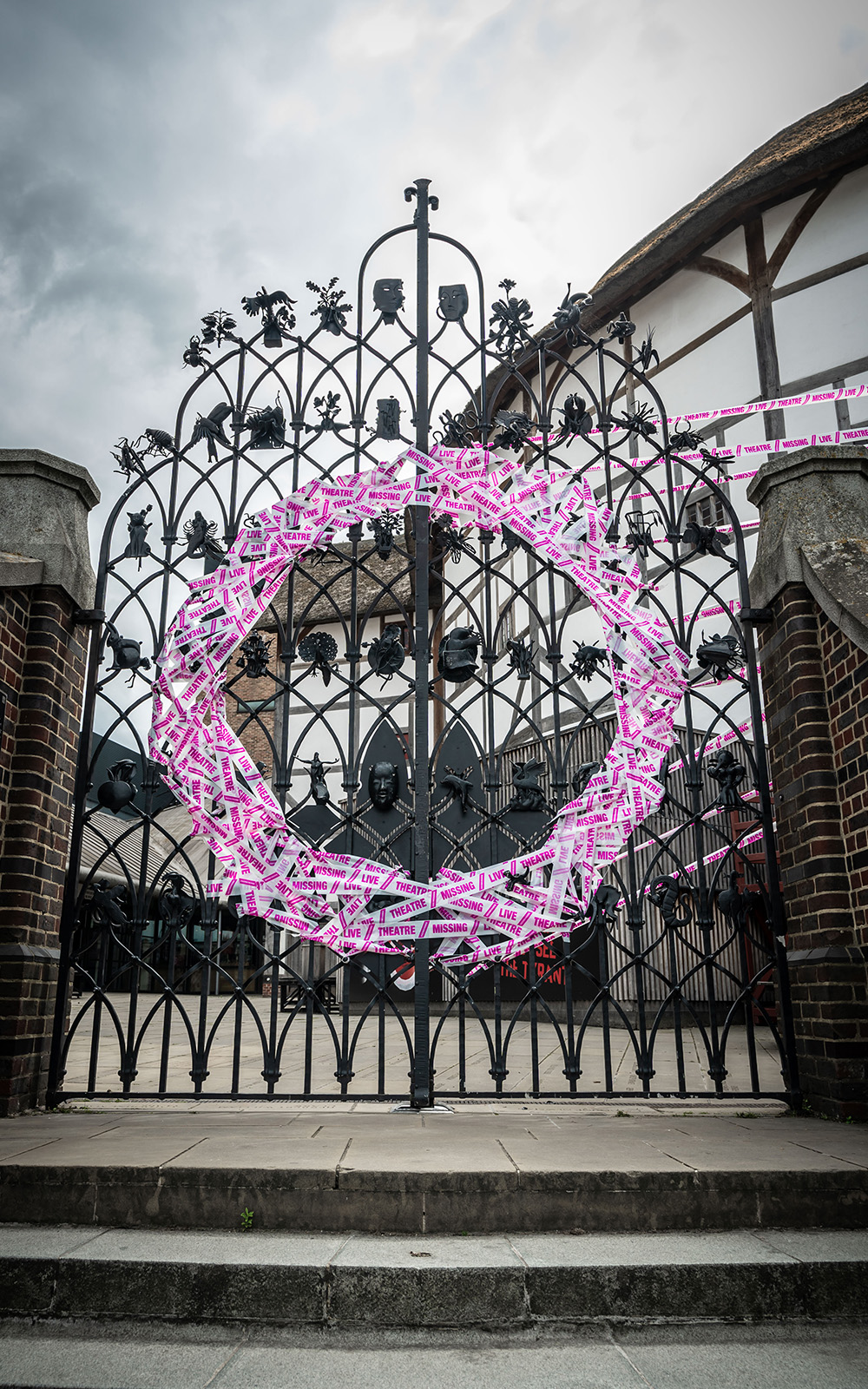 White and pink tape forms a circle on a set of iron gates.