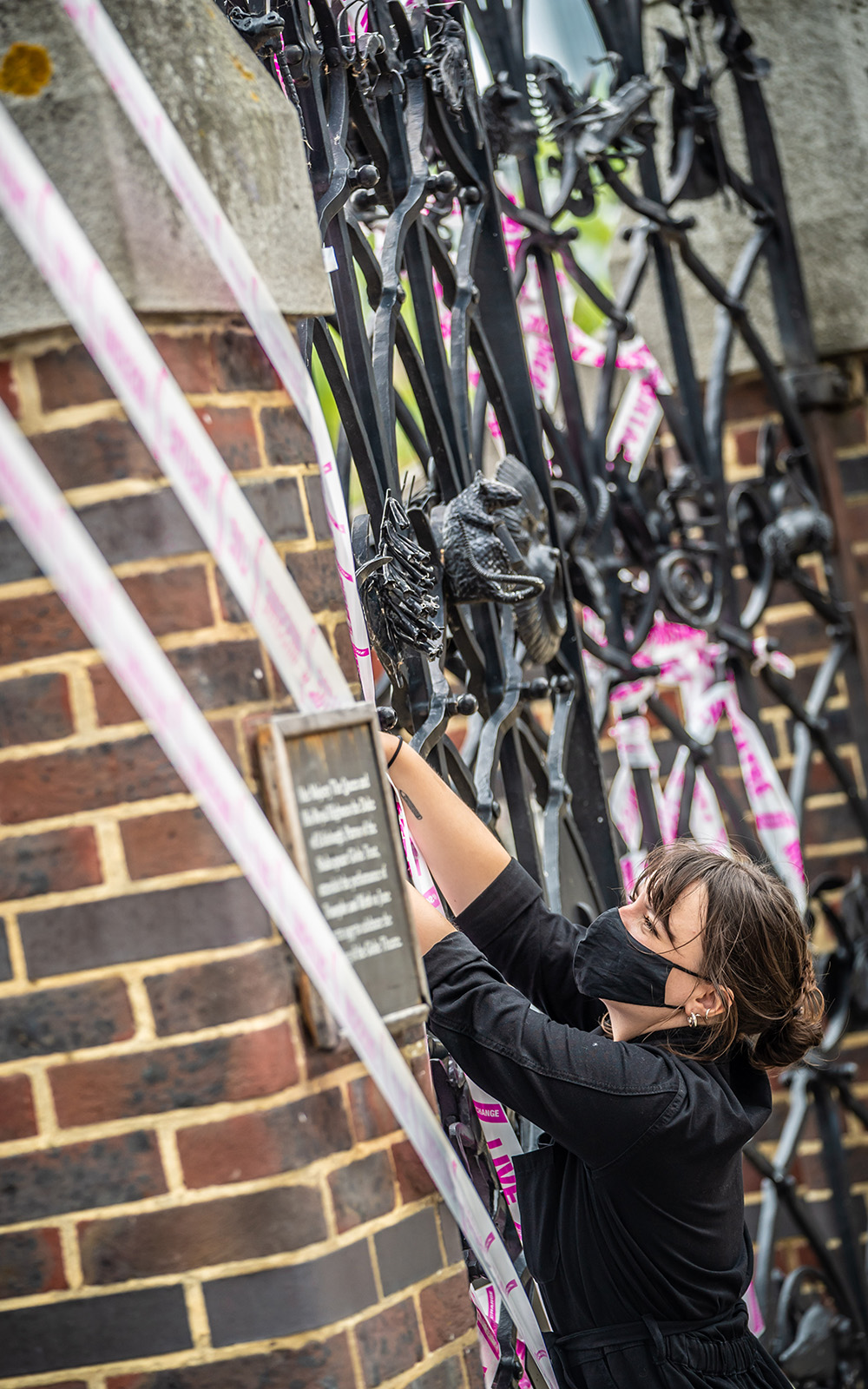 A woman leans up to adjust a piece of white and pink tape on a set of iron gates.