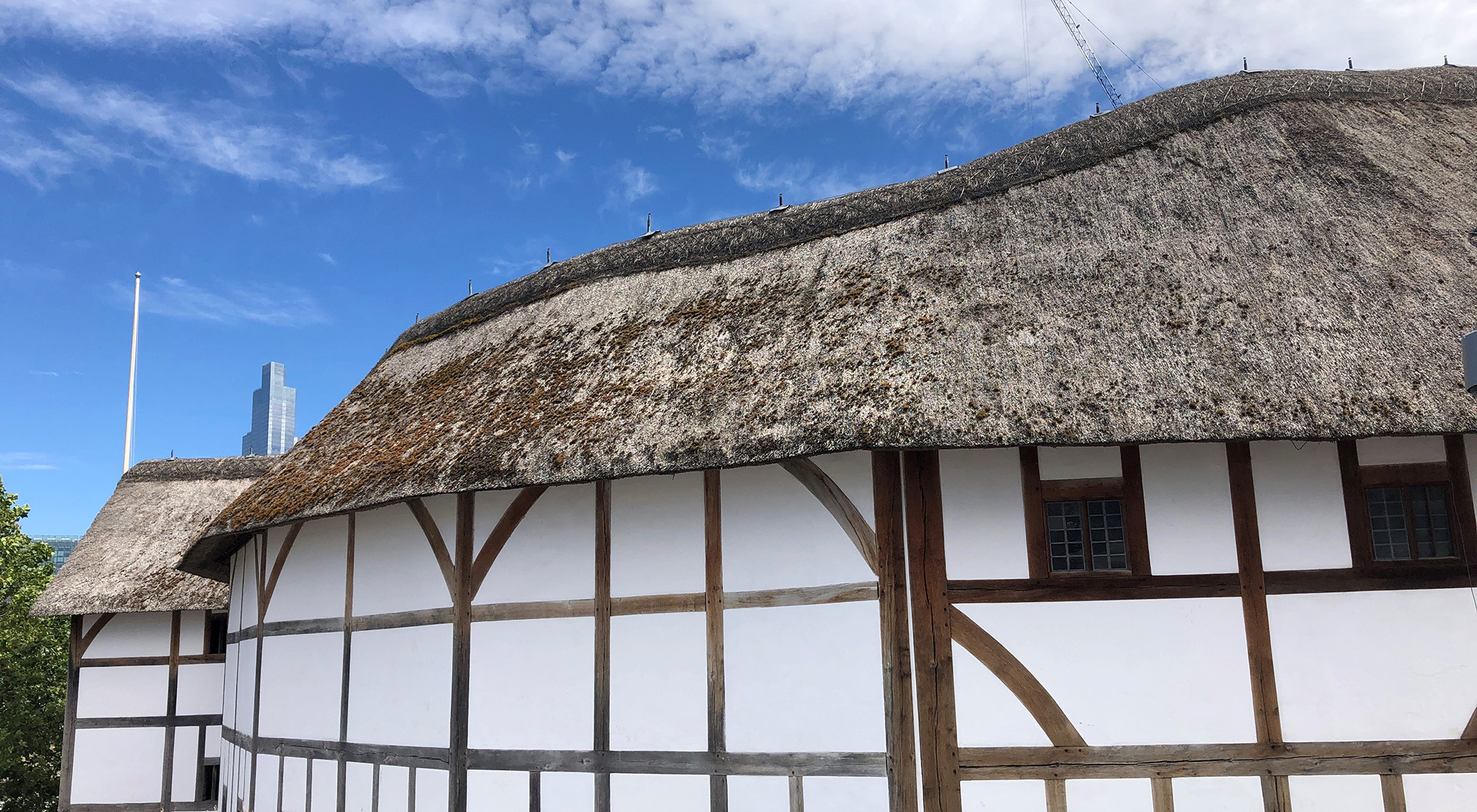 A side view looking at a white wattle and daub theatre, with a blue sky above