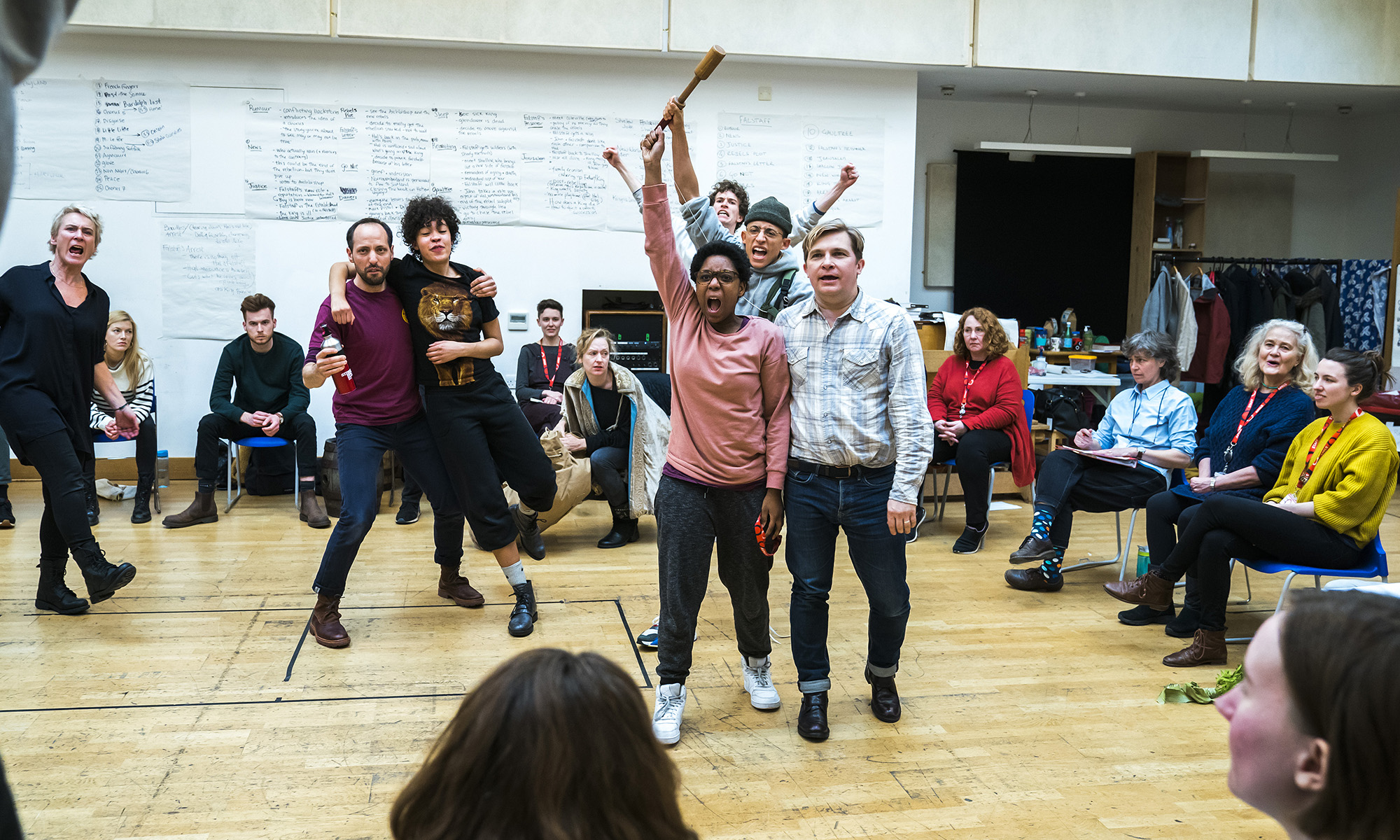 A rehearsal room with some actors punching in the air, one is being lifted, other sit around them in chairs