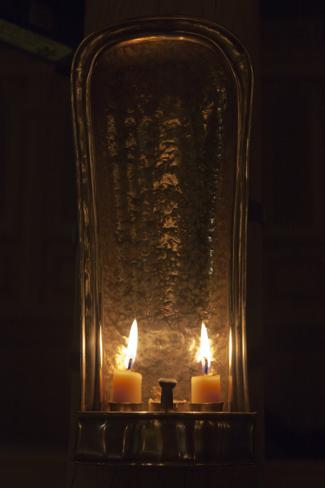 Two cream candles are lit in the darkness