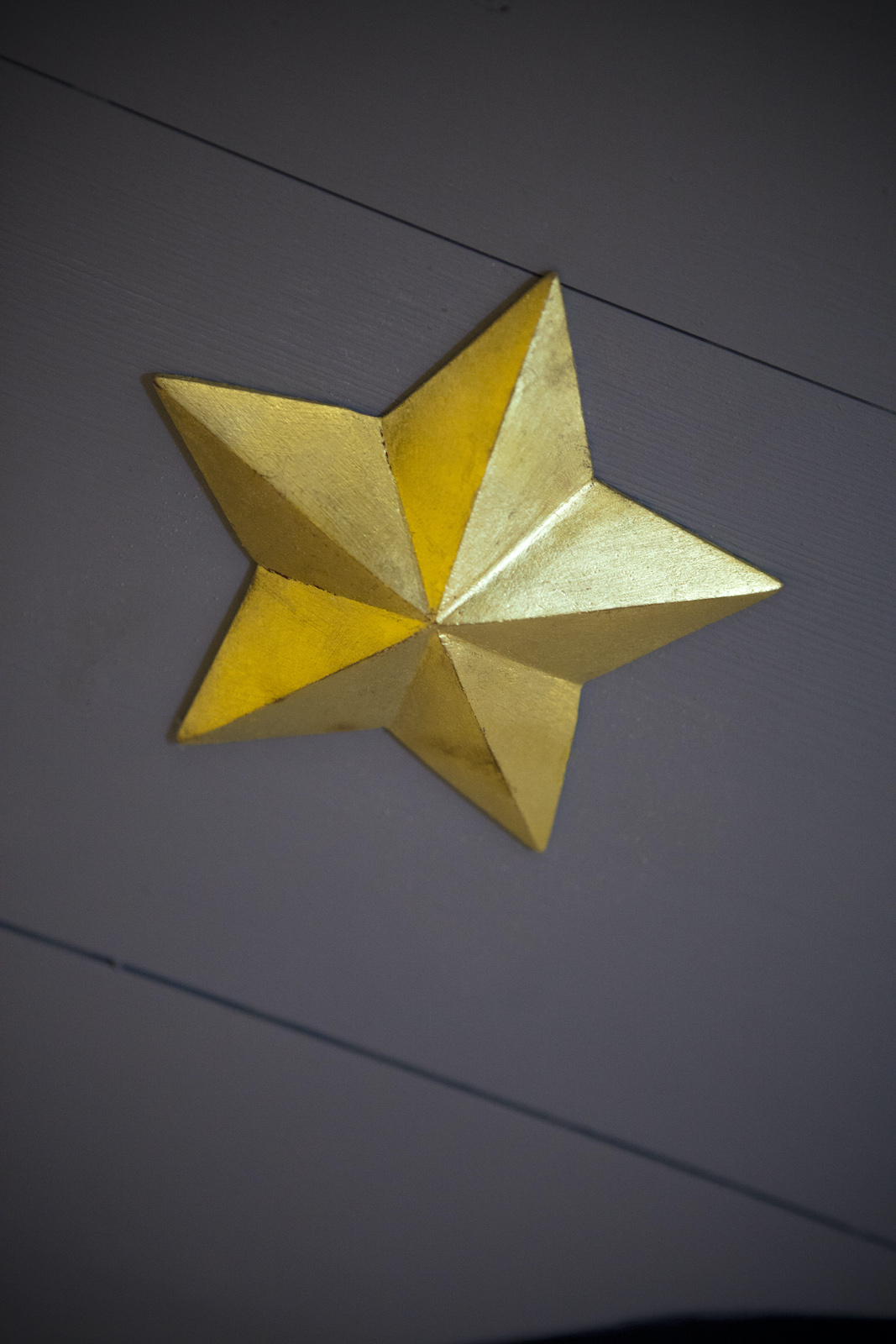 A gold star on a black wall
