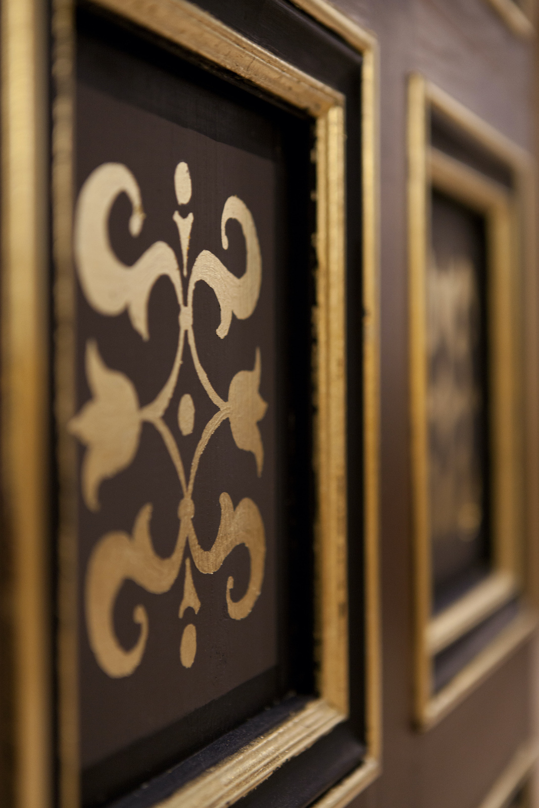 Detail on a black wall shows gold patterns