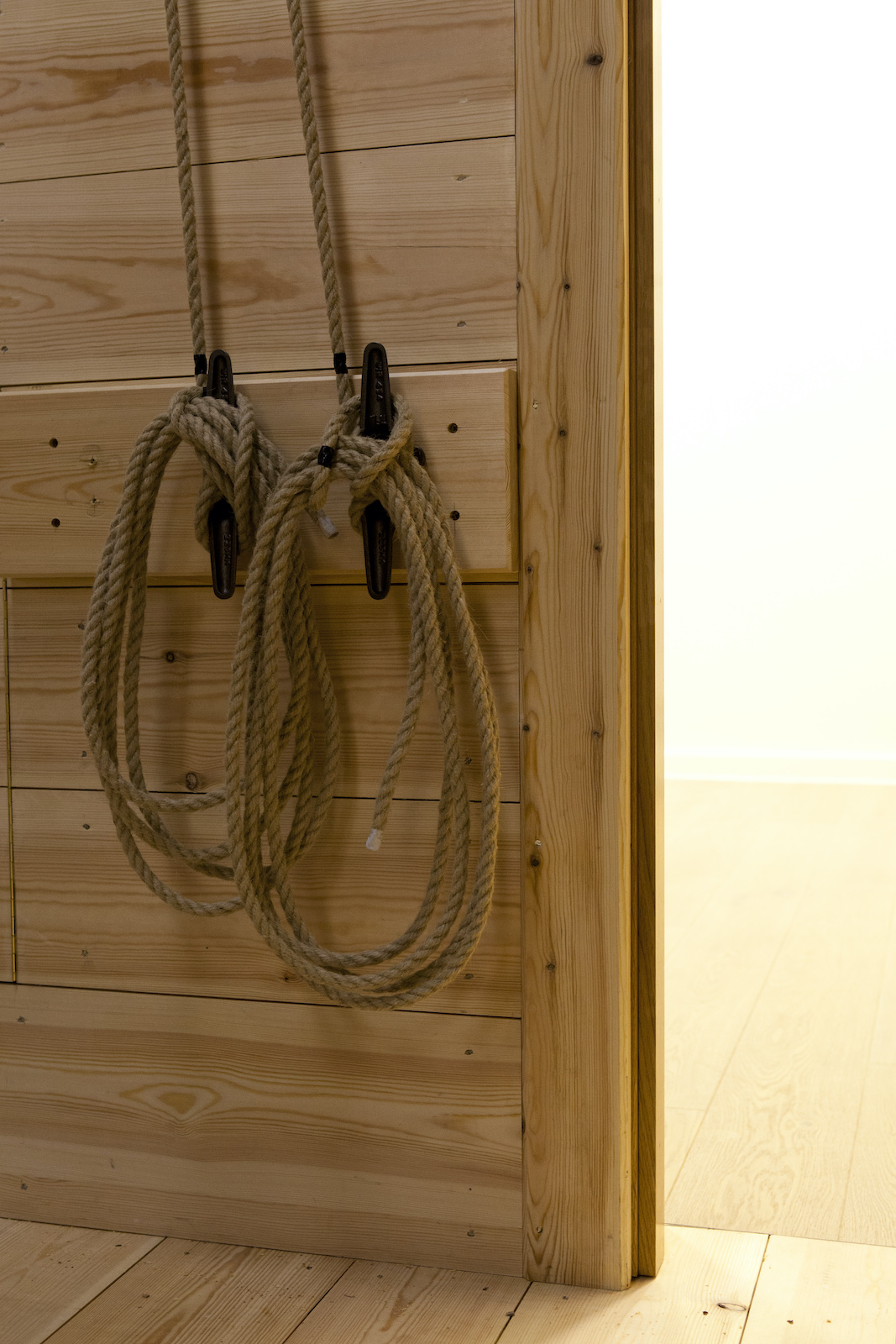 Ropes are tied to handles against a wooden wall