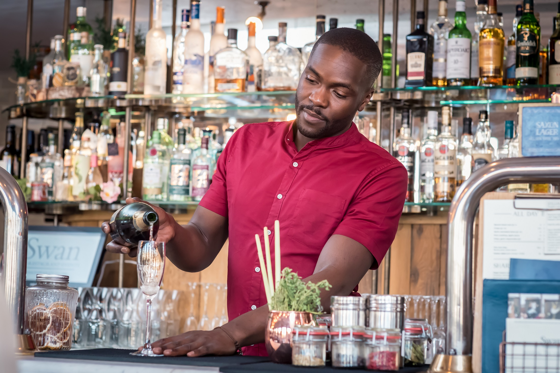 A barman in a red shirt pours a cocktail