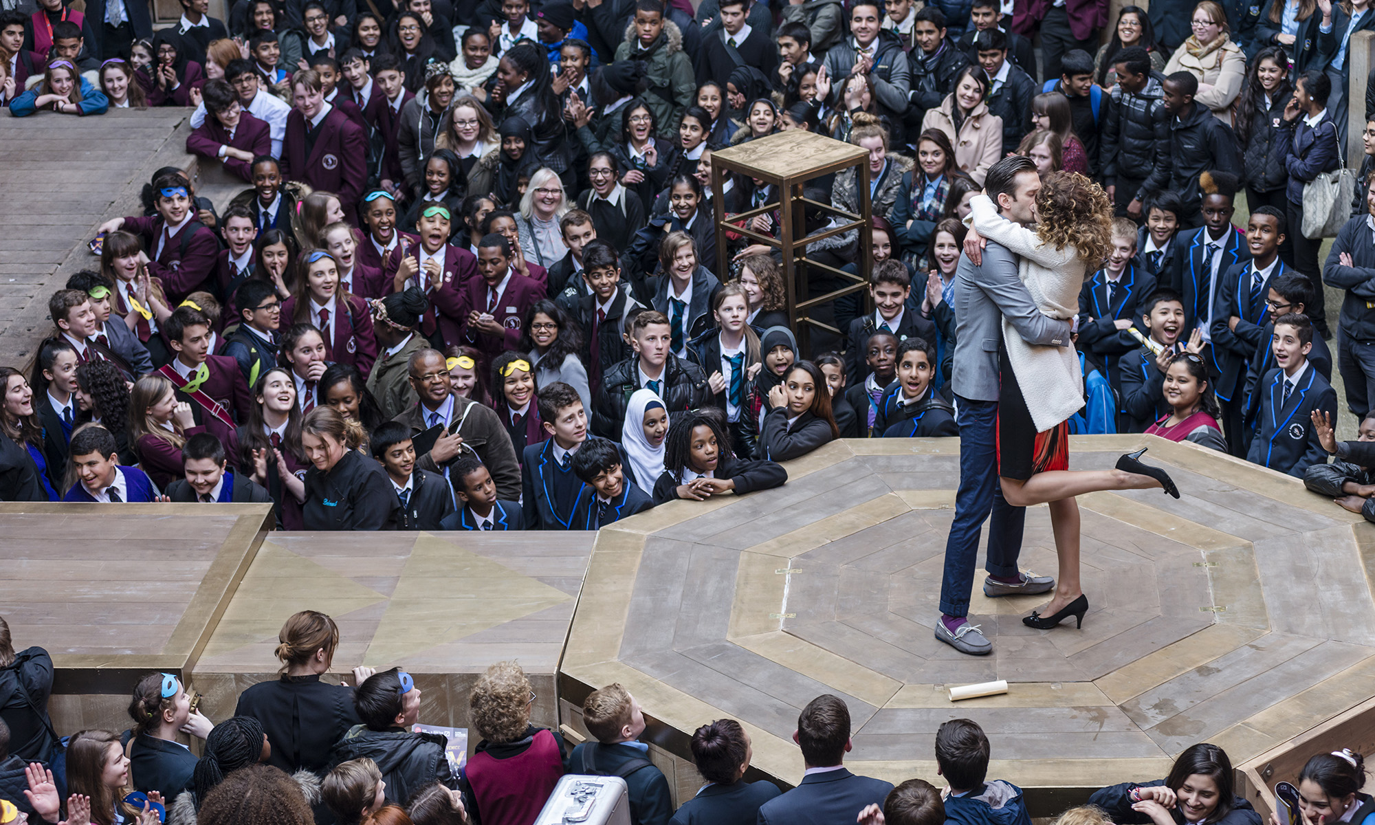 Two actors kiss on stage, on a platform that extends into the audience in the yard