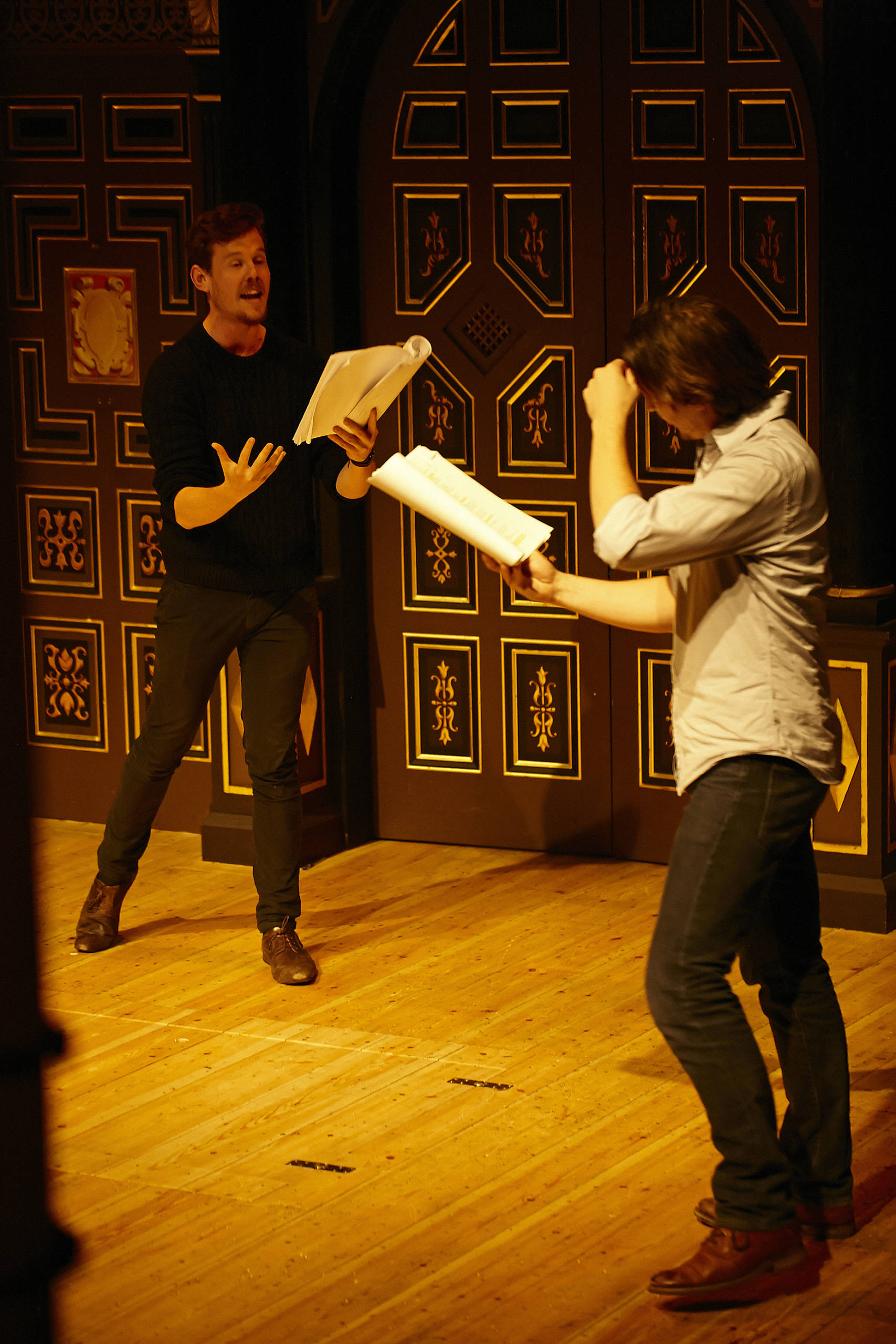 Two actors perform on stage with scripts